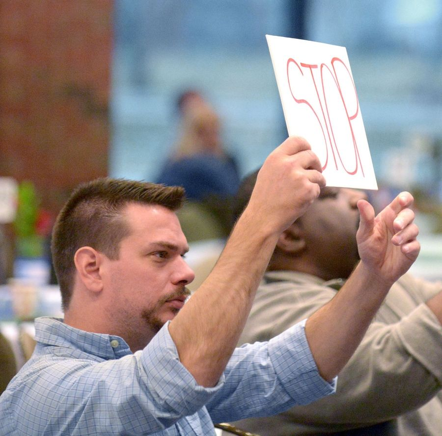"Elgin Community College business student Josh Peterson of Streamwood signals to a contestant during the ""Shark Tank 2014"" competition to wrap up their 90-second presentation Wednesday."