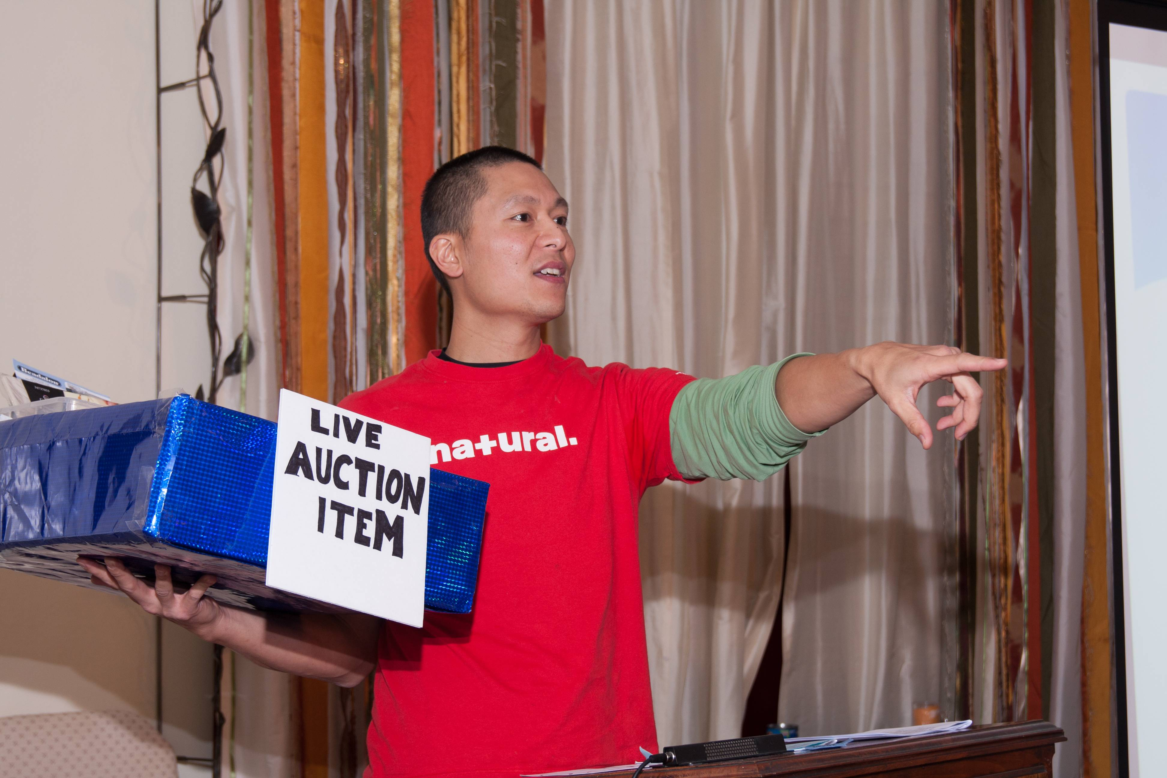 Auctioneer Chung Liang solicits bids during the auction at the Unitarian Universalist Society of Geneva which raised more than $5,000 for local charitable groups.