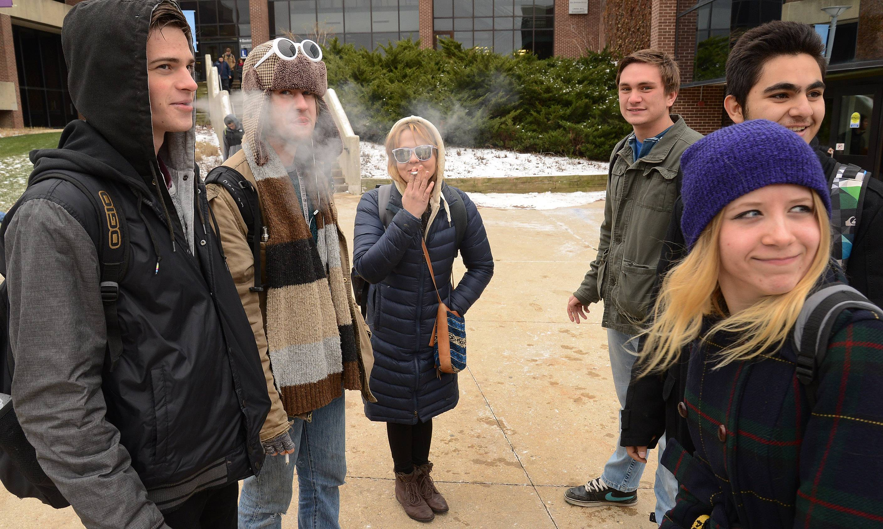 Students smoke and huddle in the cold outside Harper College in Palatine.