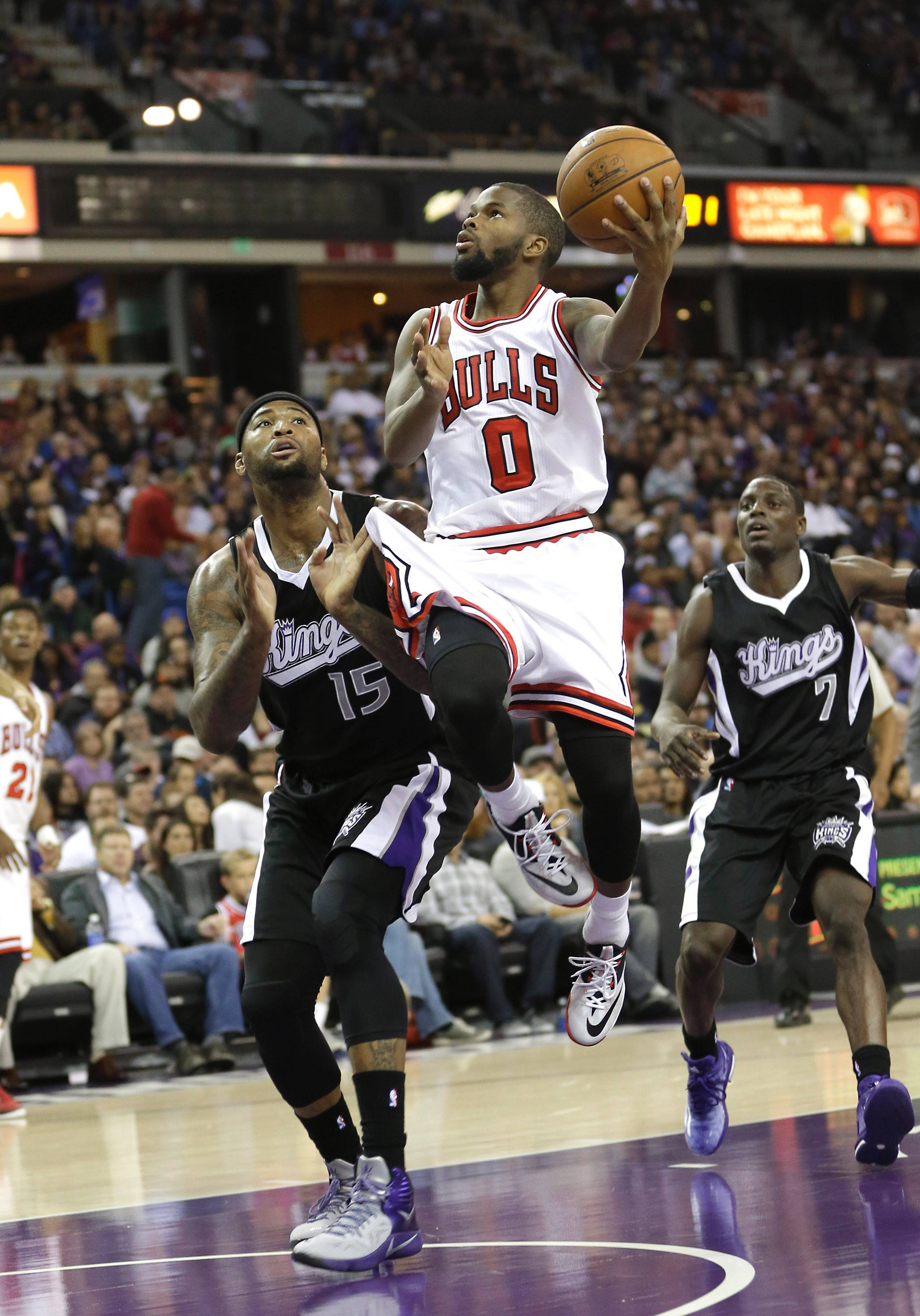 Bulls guard Aaron Brooks, center, drives to the basket against DeMarcus Cousins, as Kings guard Darren Collison, right, looks on during the first quarter their game Thursday night.