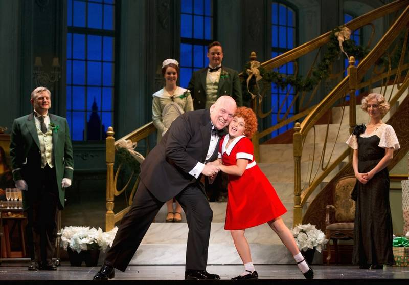 "Oliver Warbucks (Gilgamesh Taggett) and Annie (Issie Swickle) sing about her impending adoption in the number ""I Don't Need Anything But You"" as butler Drake (Todd Fenstermaker, left) and secretary Grace Farrell (Ashley Edler, right) look on in the national tour of ""Annie."" The 1977 Broadway musical plays Chicago's Cadillac Palace Theatre through Sunday, Nov. 30."