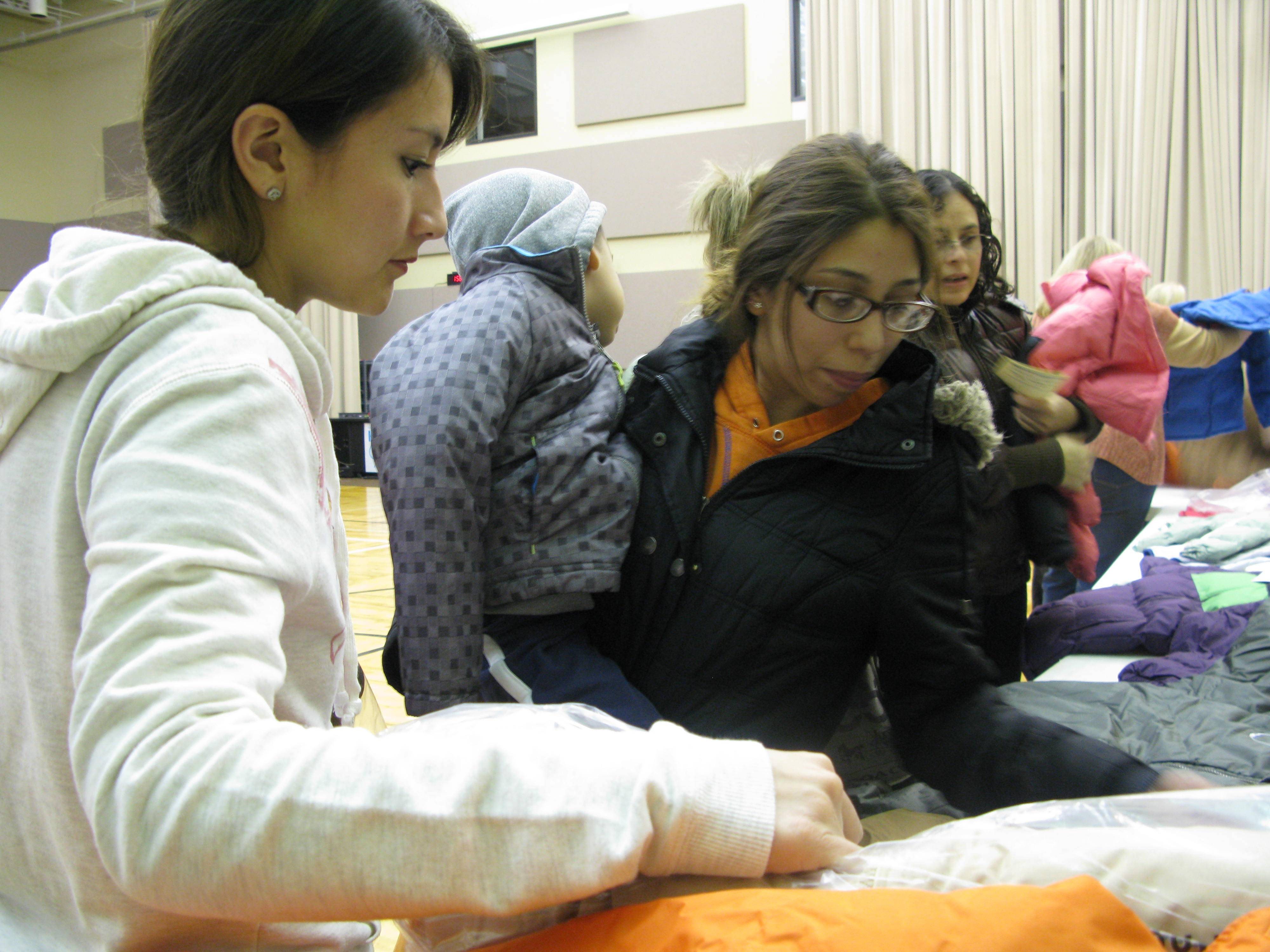 Volunteer Cara Liberacki, left, helps Mayra Munoz, of Palatine, get coats for her two children, including 2-year-old Dante Ortiz, Saturday at The Chapel in Lake Zurich during the church's annual mobile food pantry event.
