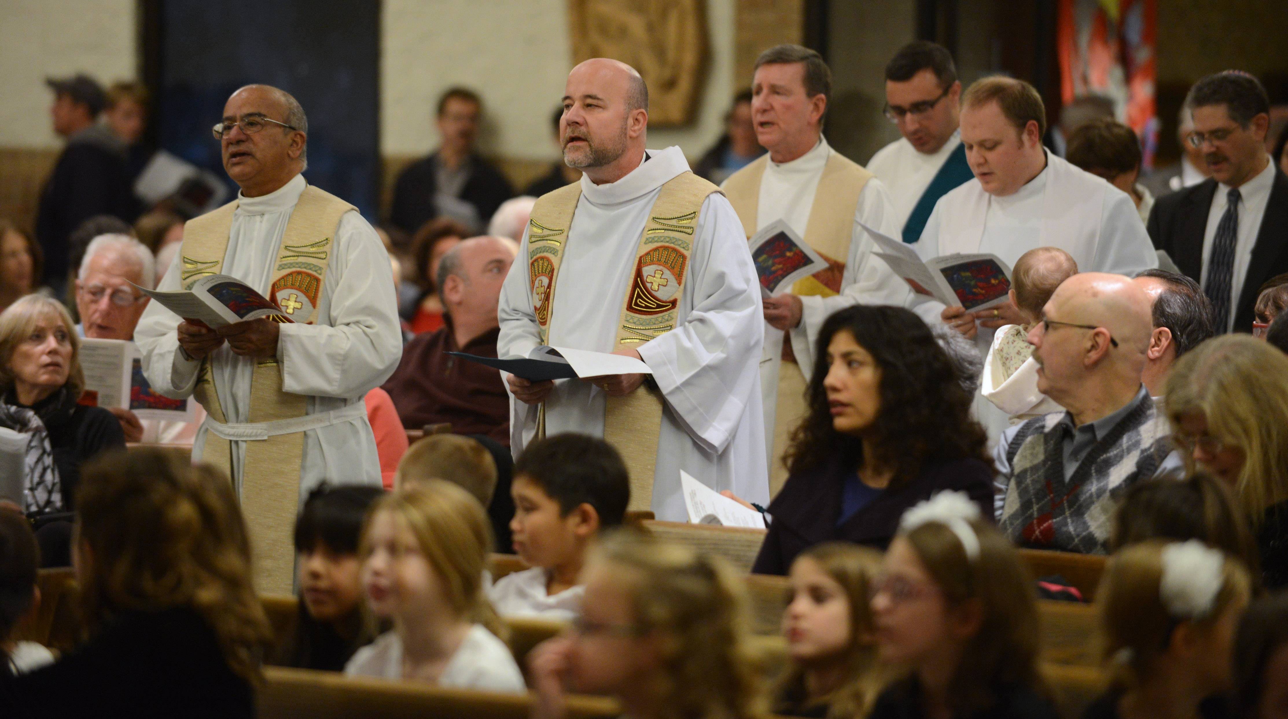 Fr. Dan Whiteside, pastor of St. Mary Church, front right, leads the processional during the Northwest Suburban's 24th annual interfaith celebration at St. Mary Catholic Church in Buffalo Grove Sunday evening.