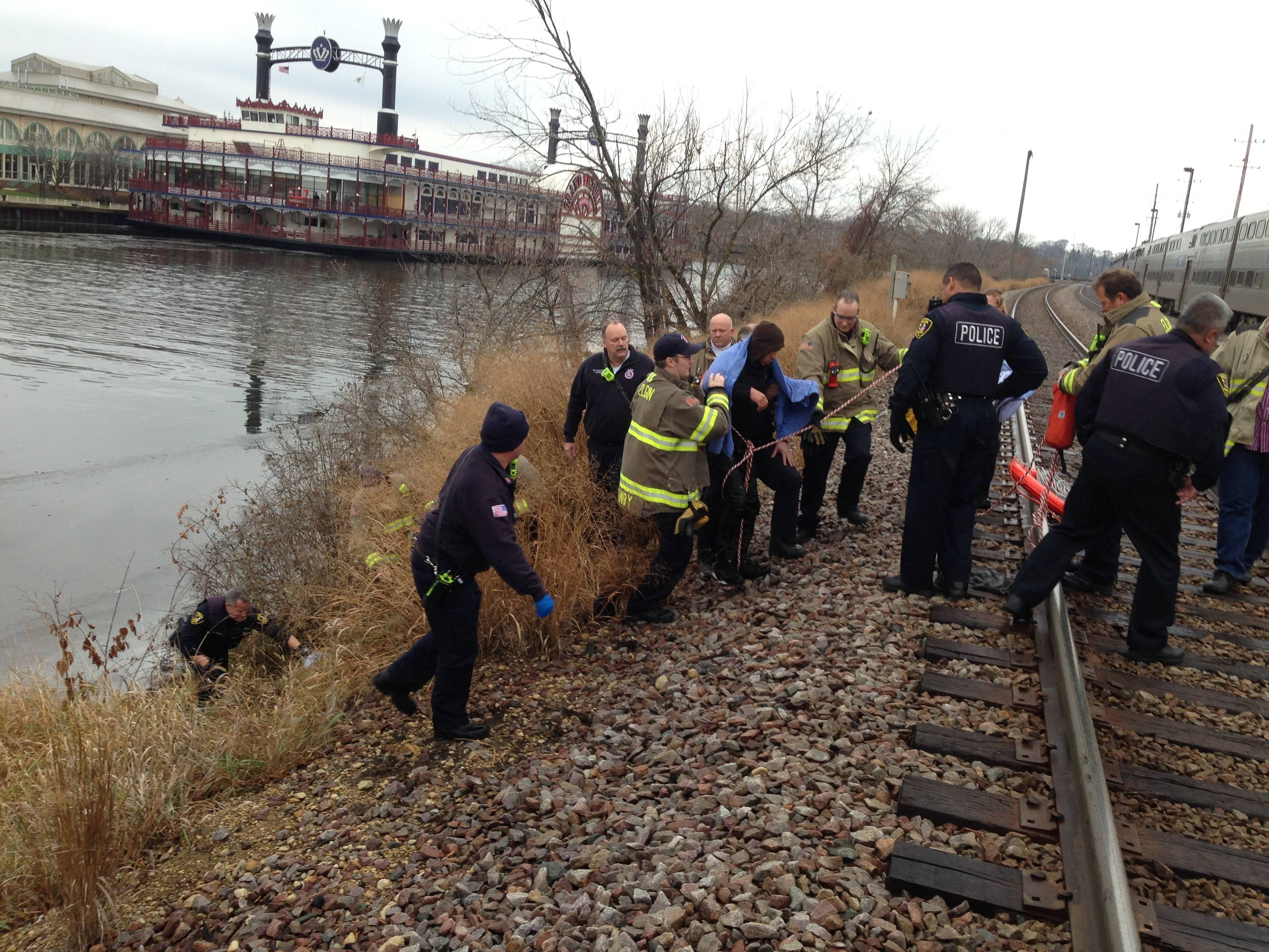 Members of the Elgin Police and Fire departments surround Melvin Ramsey, 20, of Elgin, after pulling him from the chilly Fox River Sunday morning. Ramsey fell into the river while fleeing from police officers trying to arrest him on outstanding warrants.