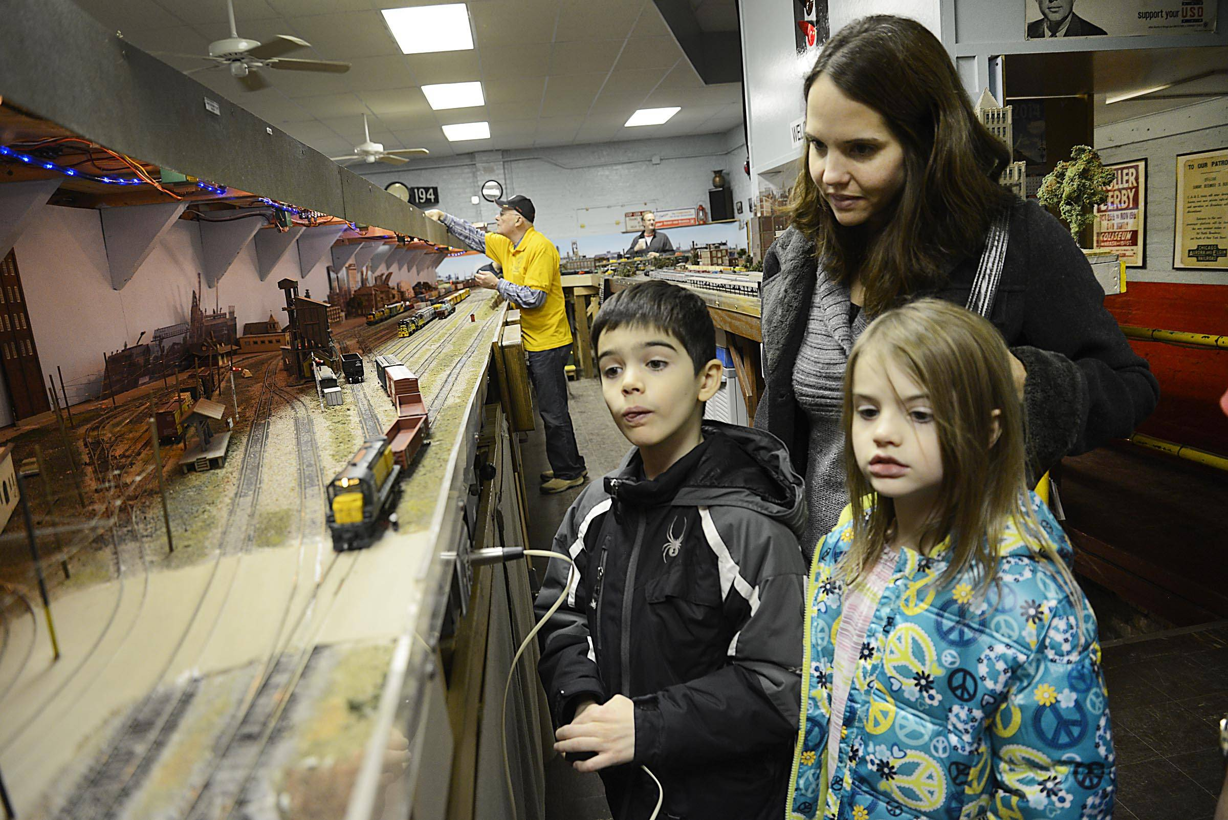 Elijah Hunt, 8, drives a model train as his sister Hannah, 6, and their mom Sarah, of Elgin, watch at the 65th annual Valley Model Railroad Club open house Sunday at the Clintonville Station in South Elgin.
