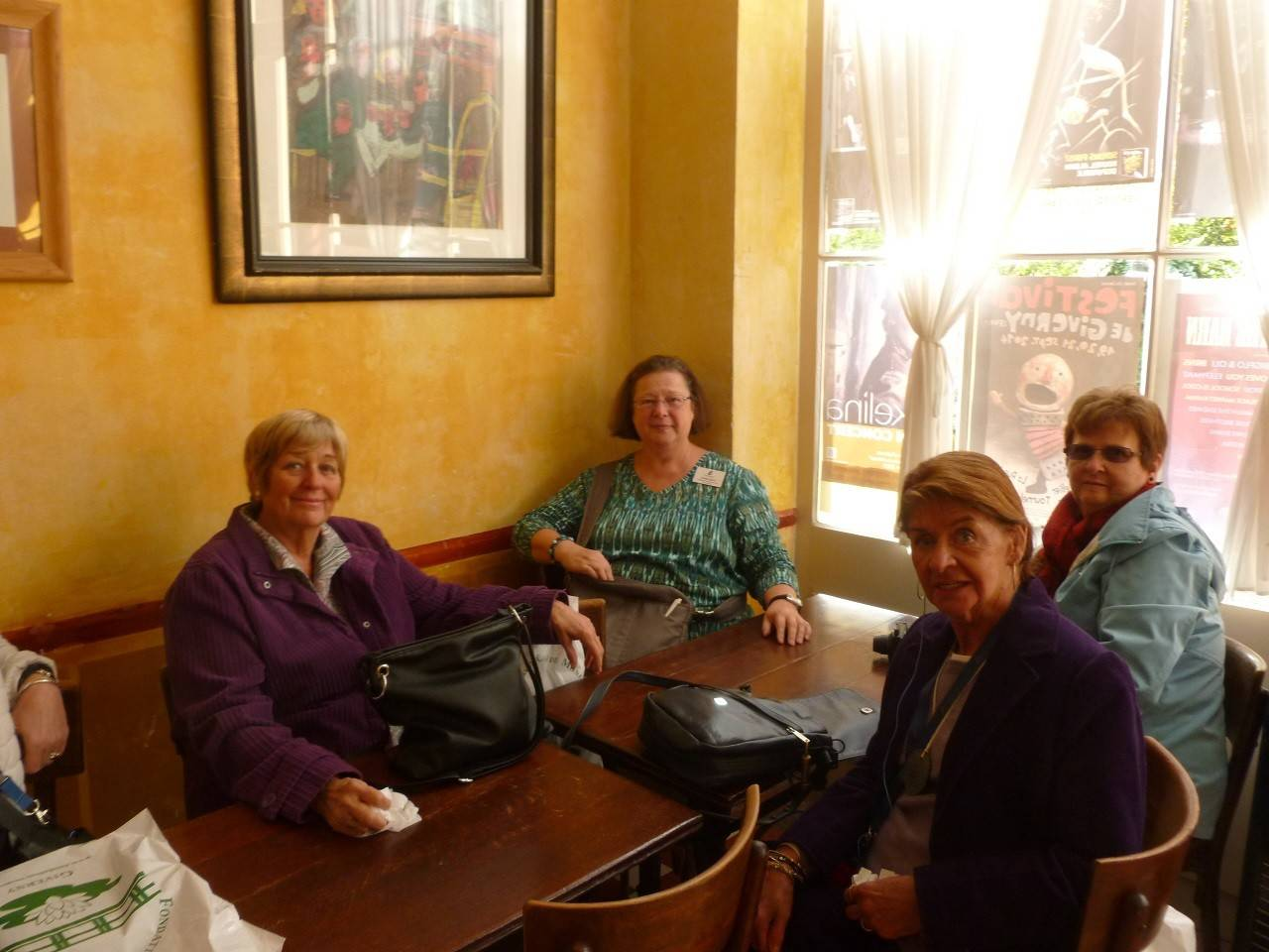 Community Education Travel manager Linda Kerr (center) sits with a few members of a group she led to Paris and Normandy, France. Here they wait for tea in the Hotel Baudy in Giverny, France, a frequent haunt of the artist Claude Monet.