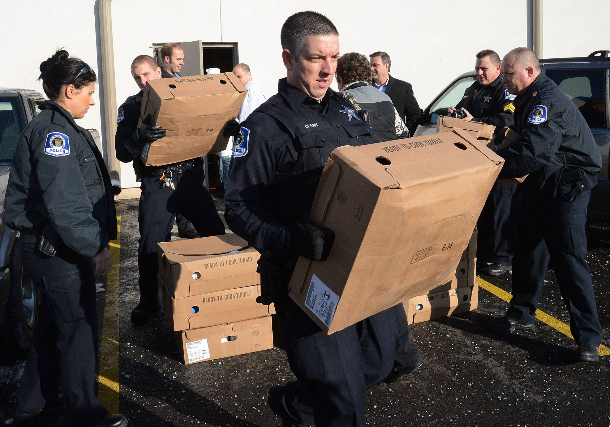 Officer Scott Clark hauls off a box of turkeys, as the Mundelein Police Department and Elly's Pancake House in Mundelein team up Tuesday to provide families in need with a complete Thanksgiving meal. In all, 75 turkeys were delivered.