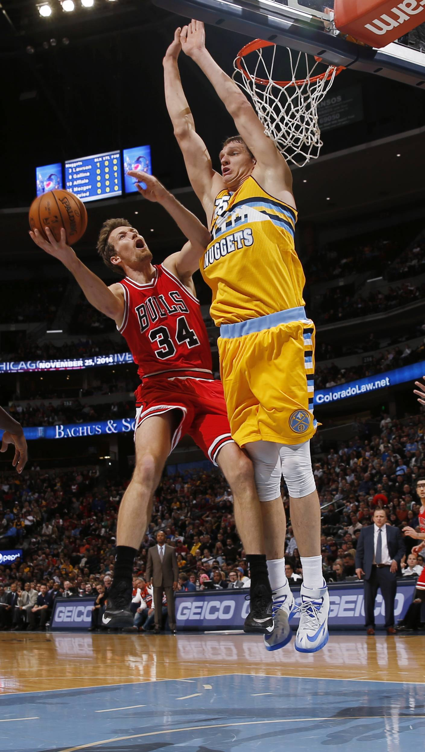 Bulls forward Mike Dunleavy drives the lane for shot as Nuggets center Timofey Mozgov defends Tuesday night at Denver.