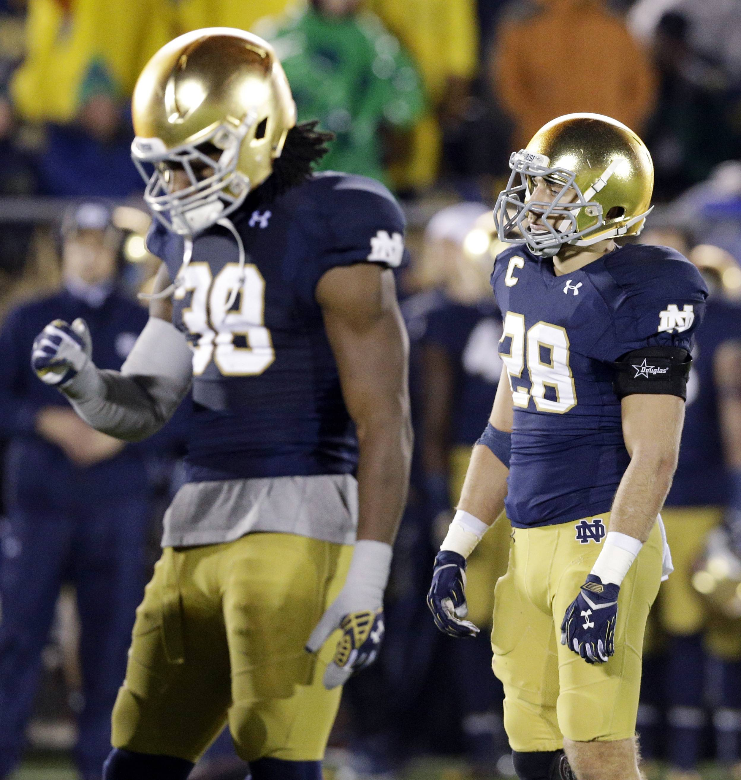 Notre Dame safety Austin Collinsworth, right, and linebacker Joe Schmidt react to their 31-28 loss to Louisville on Saturday in South Bend, Ind.