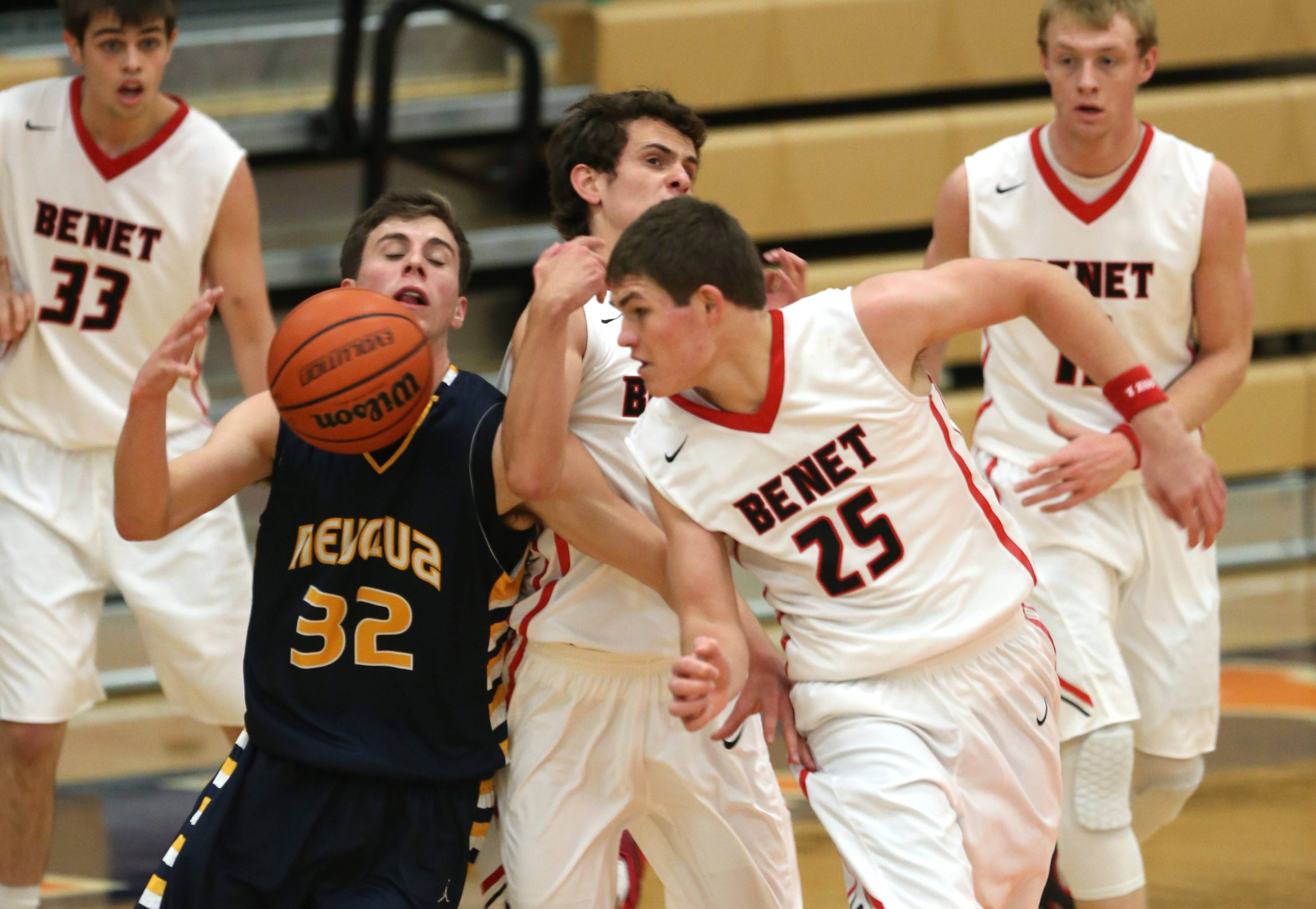 Neuqua Valley's Connor Raridon, left, looks to gain possession while guarded by Benet's Sean Liska, center, and James Dockery, right, during the Hoops for Healing boys basketball tournament at Oswego High School.