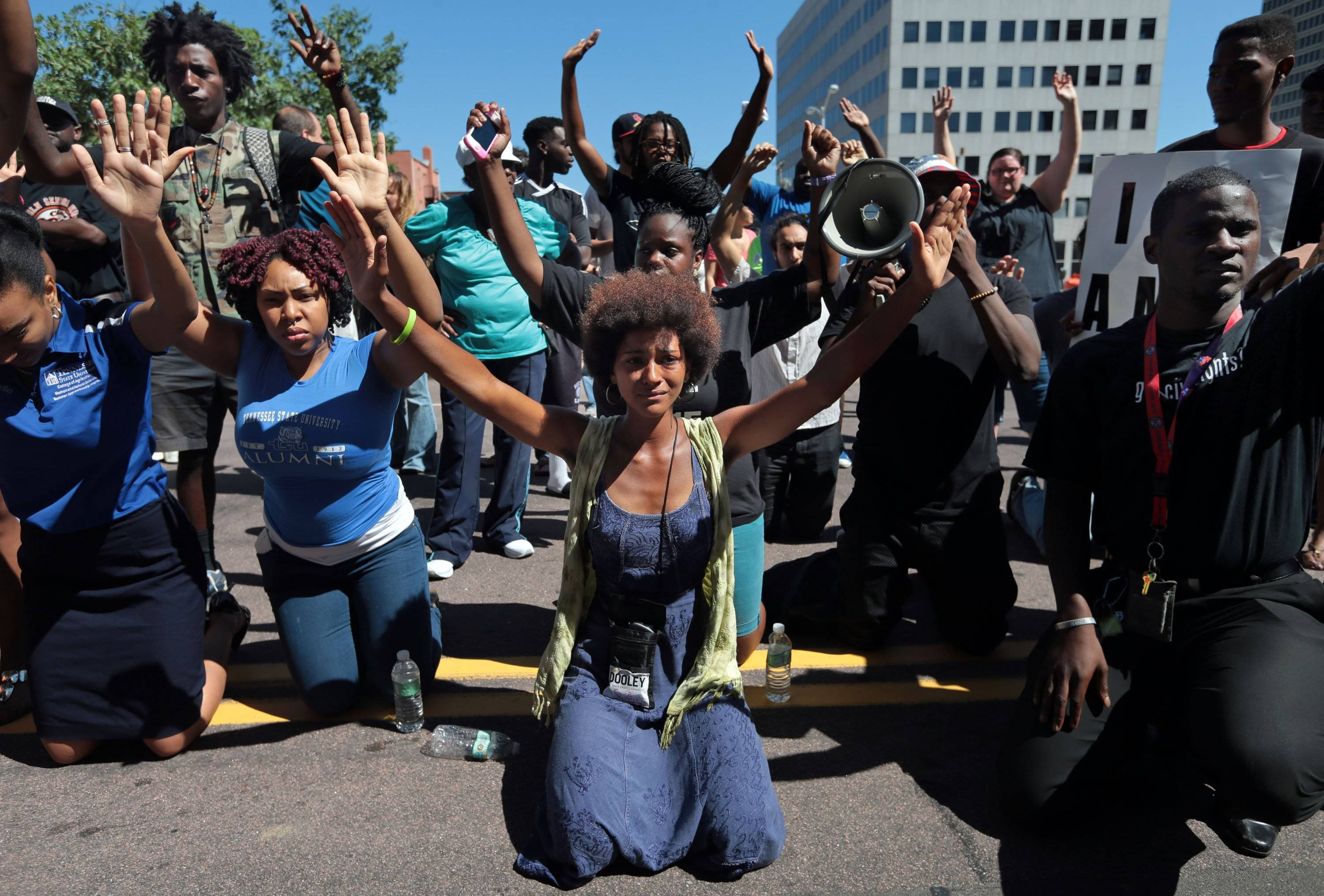 Protestors drop to their knees and put their arms in the air during a rally for Michael Brown, who was shot and killed by a Ferguson police officer, in Clayton, Mo., in this Aug. 12 file photo.