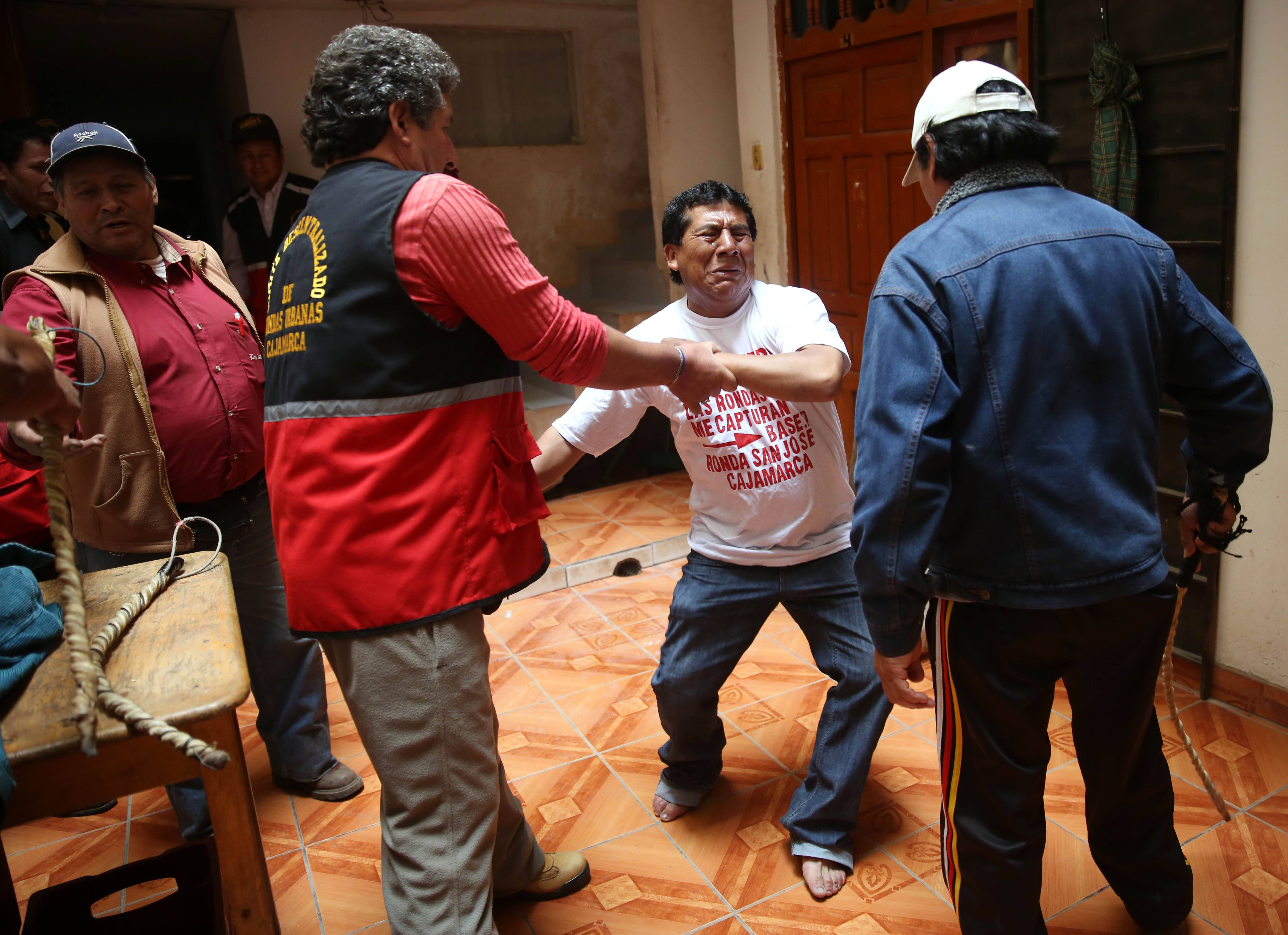 "An alleged serial pickpocket tries to evade a lashing by citizen vigilantes known as ""rondas urbanas"" in Cajamarca, Peru, in this May 12 file photo. After a dozen lashes, he confessed, and paid $60 to a woman whose cell phone he had allegedly stolen."