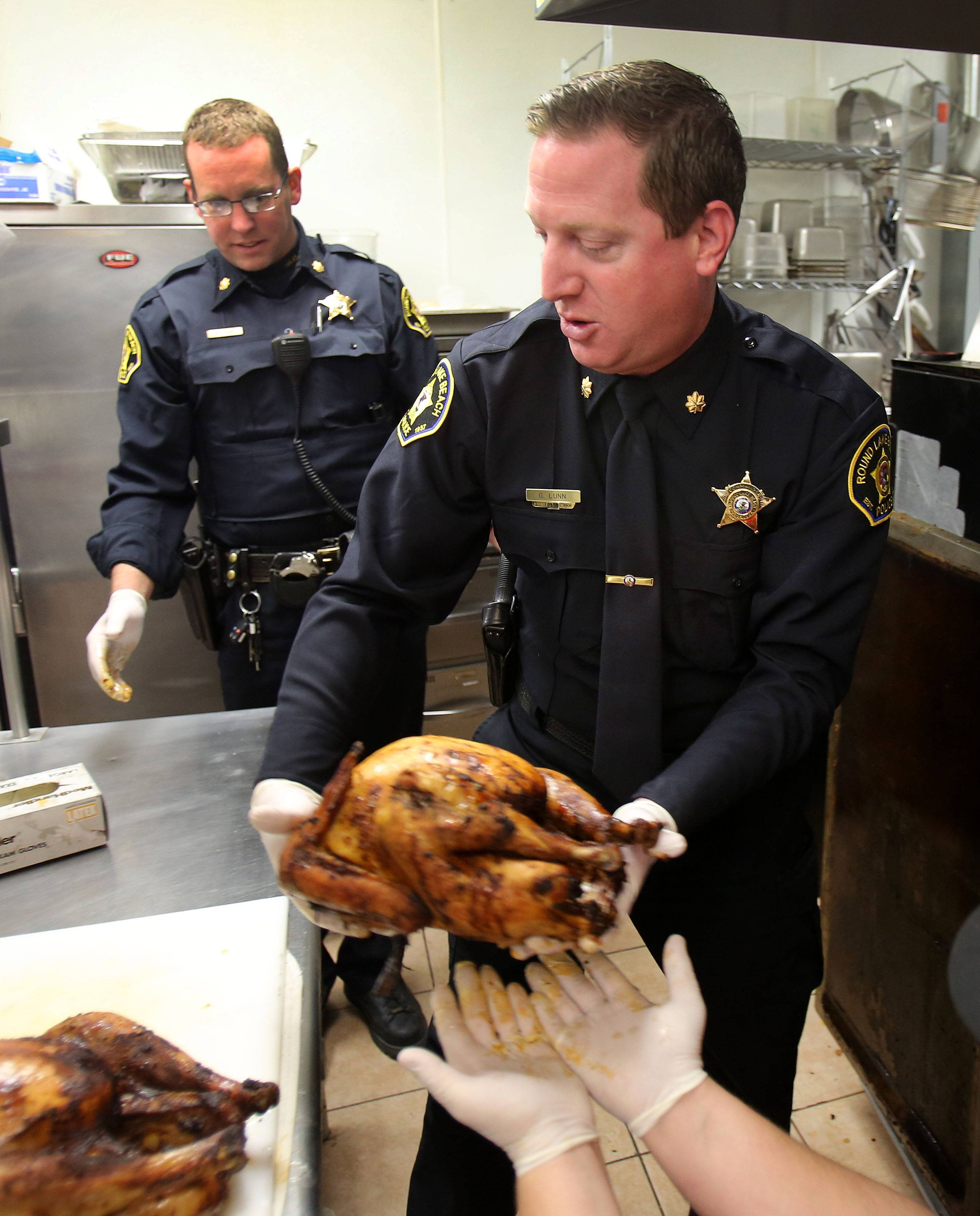 Round Lake Beach Police Cmdr. Gary Lunn, right, and Officer Mike Barr pull turkeys out of a smoker at BBQ'd Productions in Third Lake as they prepare Thanksgiving dinners for area families Thursday.