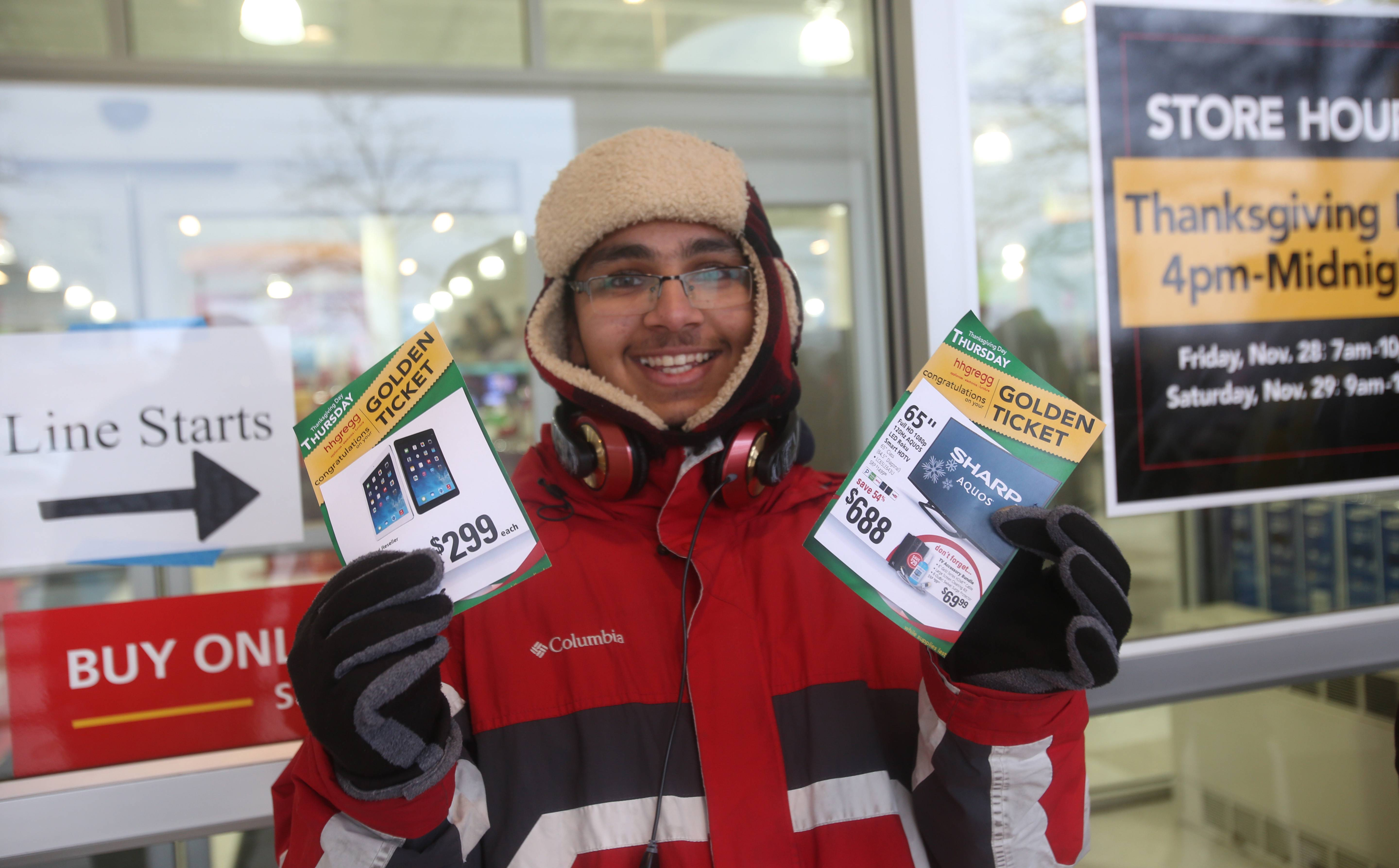 Rishabh Saxena of Hoffman Estates is first in line Thanksgiving night and displays a golden ticket to get a discounted iPad and flatscreen TV at the HHGregg Appliances and Electronic Store in Schaumburg .