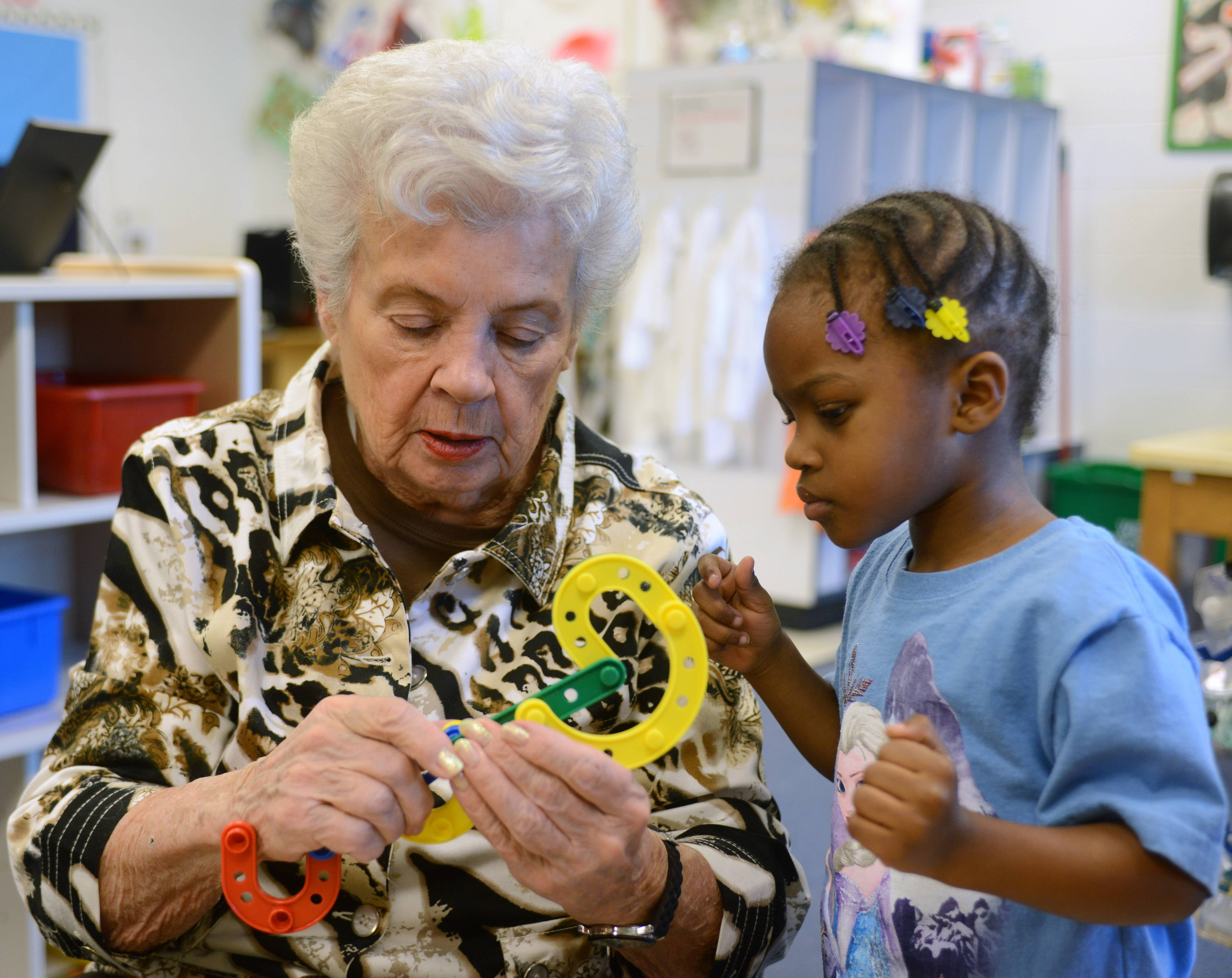 "Pat Hollerbach, also known as ""Grandma Pat,"" is an 85-year-old classroom volunteer at John G. Conyers Learning Academy in Rolling Meadows. Here she helps Khamryne McDonald assemble a toy."