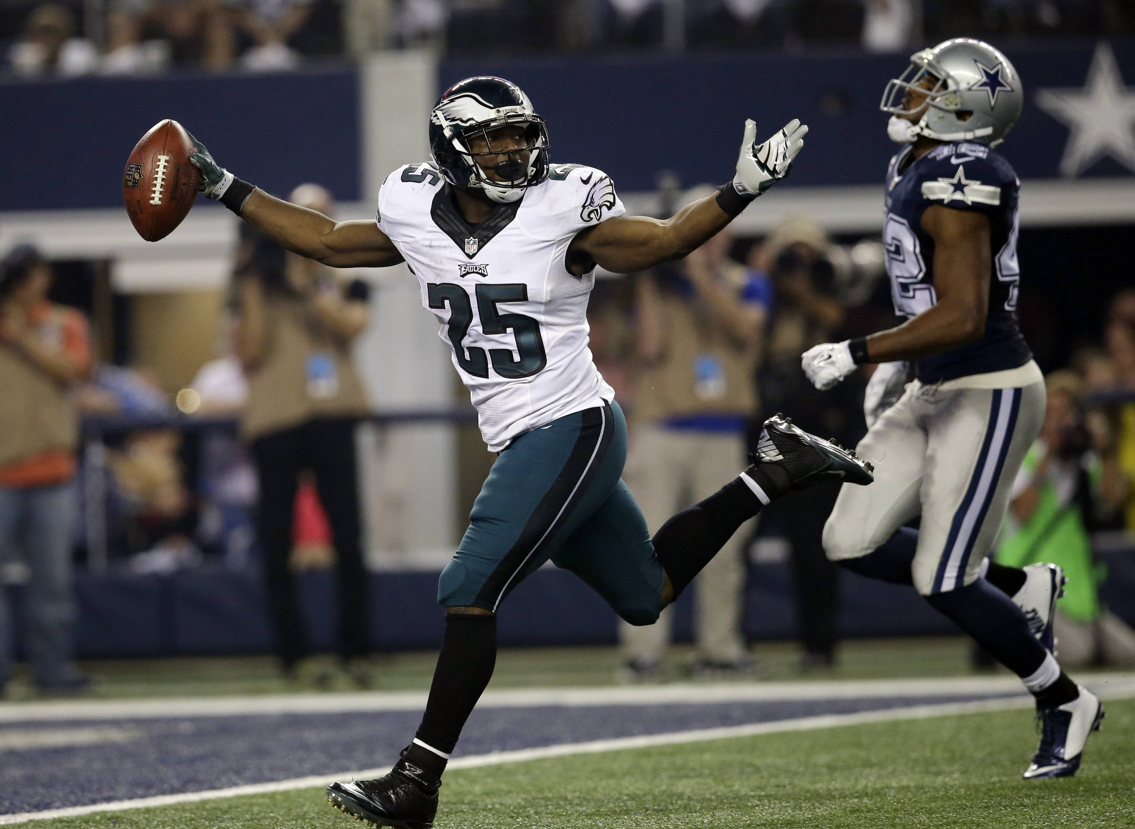 Philadelphia Eagles' LeSean McCoy (25) celebrates in front of Dallas Cowboys' Barry Church (42) as he sprints into the end zone for a touchdown during the second half of an NFL football game, Thursday, Nov. 27, 2014, in Arlington, Texas.