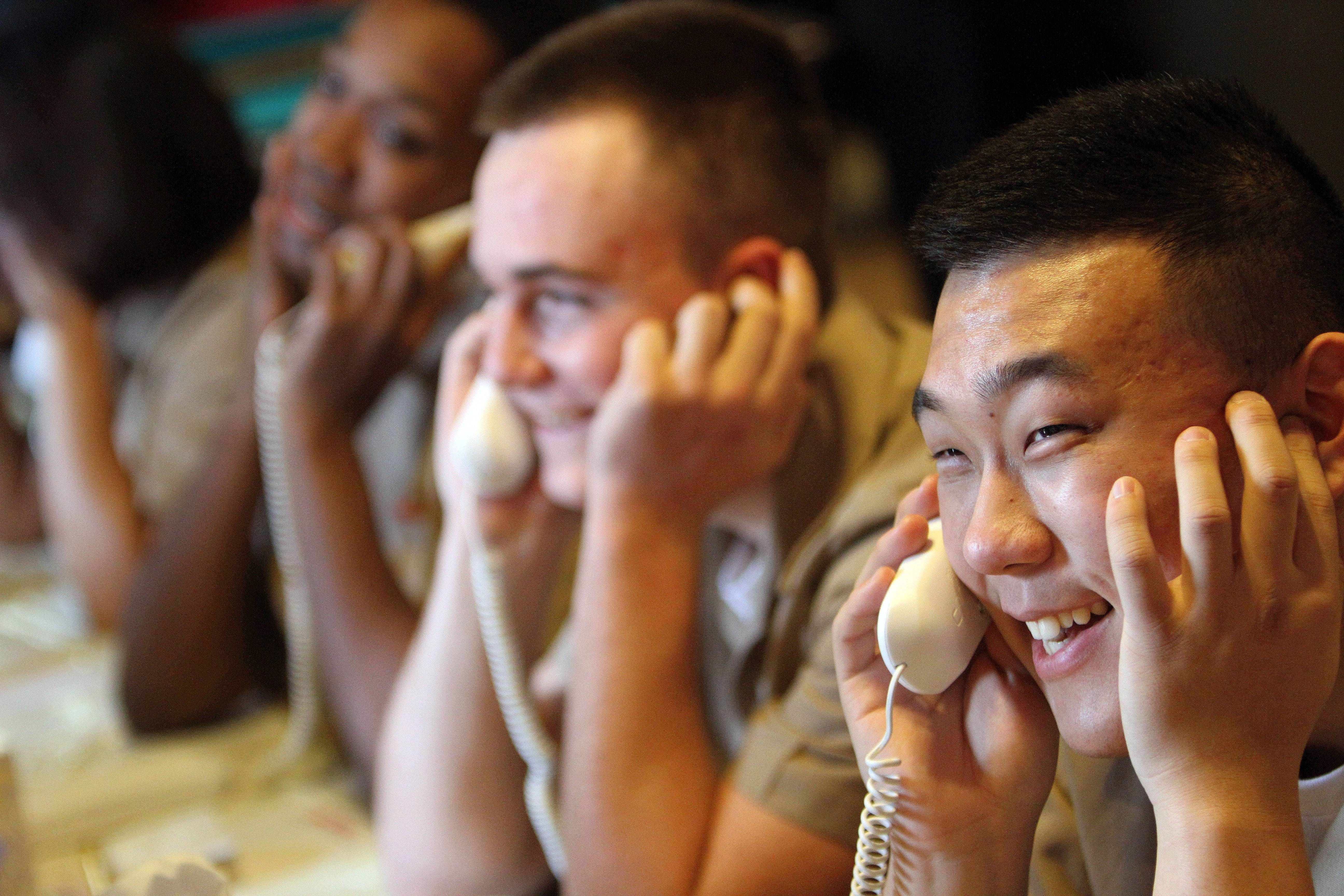 Recruits from the Great Lakes Naval Station's recruit training command call home during a Thanksgiving event at the American Legion hall in Arlington Heights Thursday.