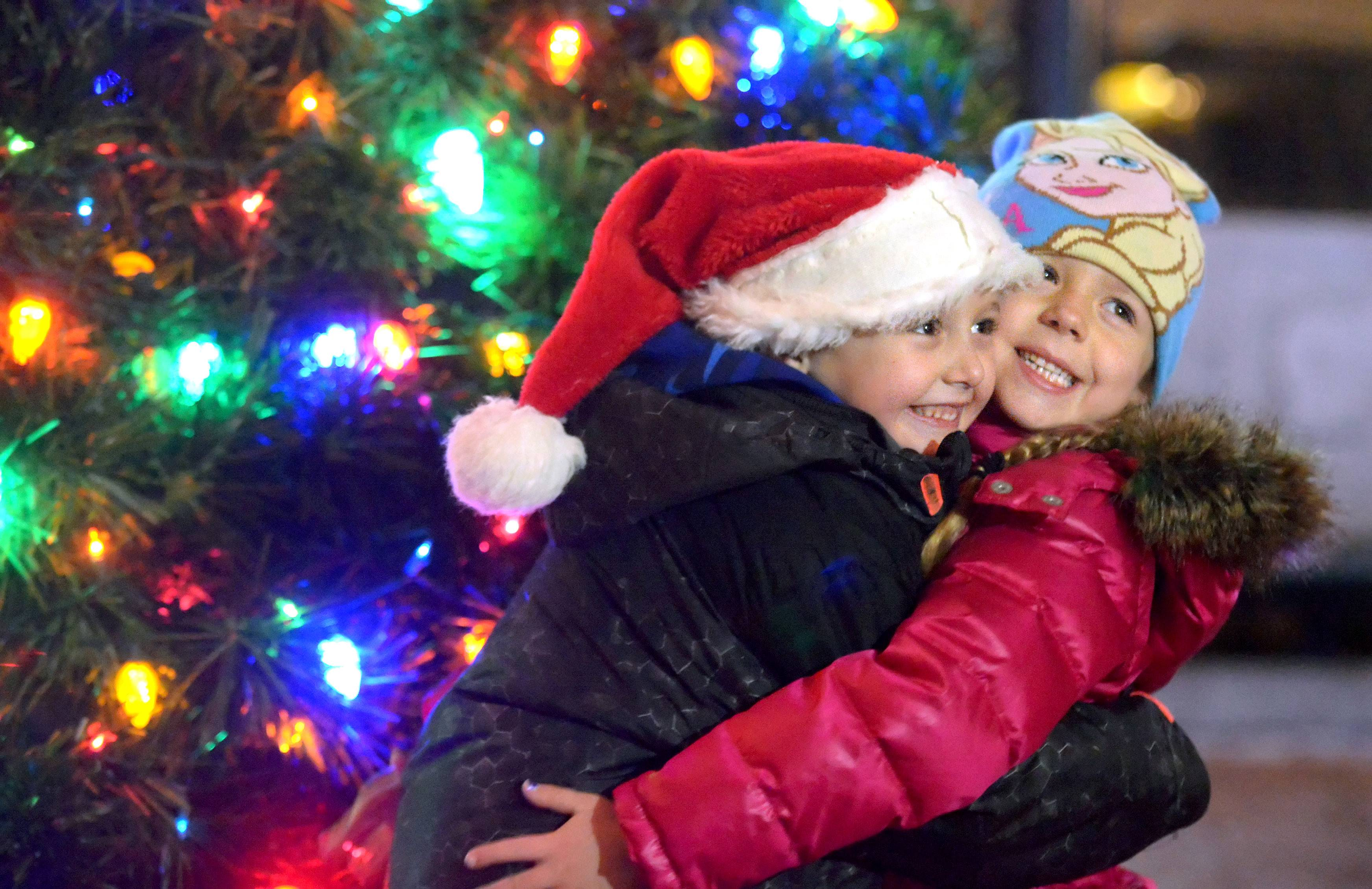 Cousins Frankie Graves, 6, and Aubree O'Dell, 4, both of St. Charles, embrace for a photo for their aunt Donna Honeyman of St. Charles in front of one of the trees in the First Street Plaza at the St. Charles Holiday Homecoming Friday night. The duo have been coming ever since they were born; their aunt has been coming since the 1970s.