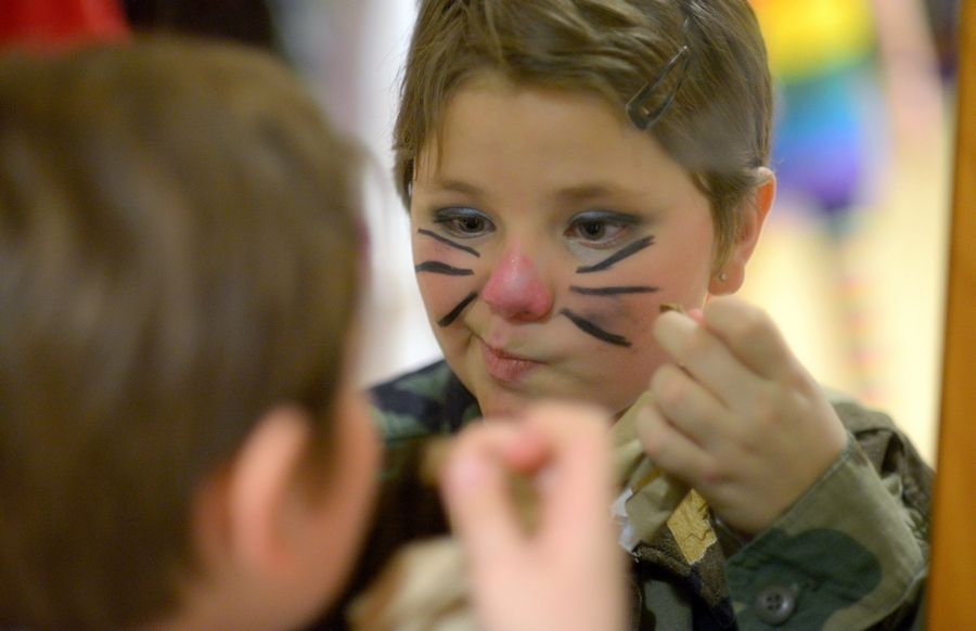 "Jayd Steinke fixes a smudge in her Cat in the Hat whiskers makeup between scenes while rehearsing ""Seussical Jr."" recently in St. Charles."