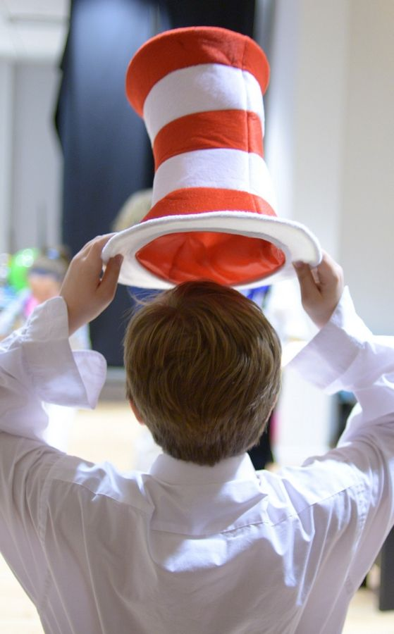 "Jayd Steinke, 10, of St. Charles dons her striped top hat before taking to the stage for rehearsal of ""Seussical Jr."" in St. Charles."