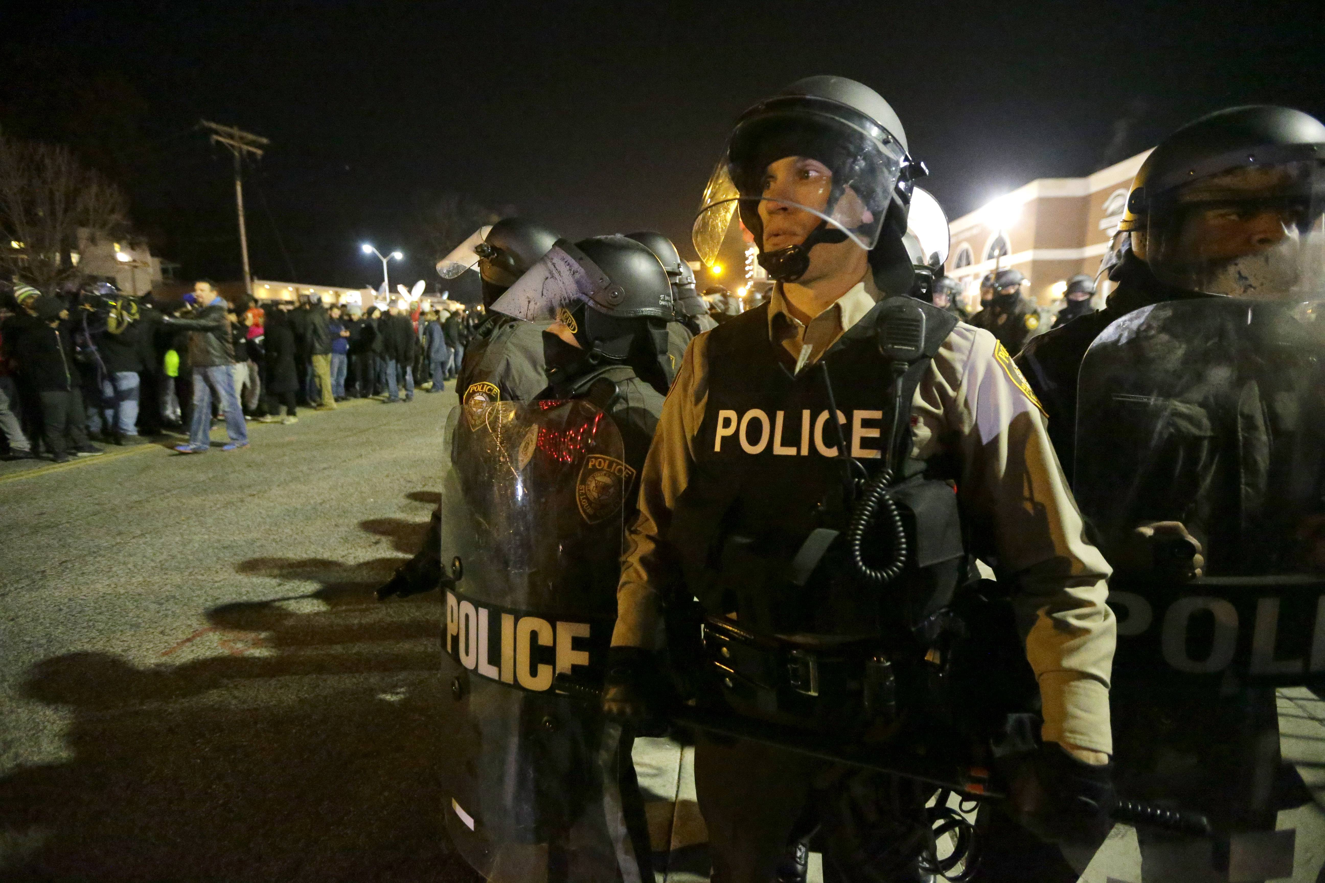 Police watch the street as protesters gather Tuesday in Ferguson, Mo.