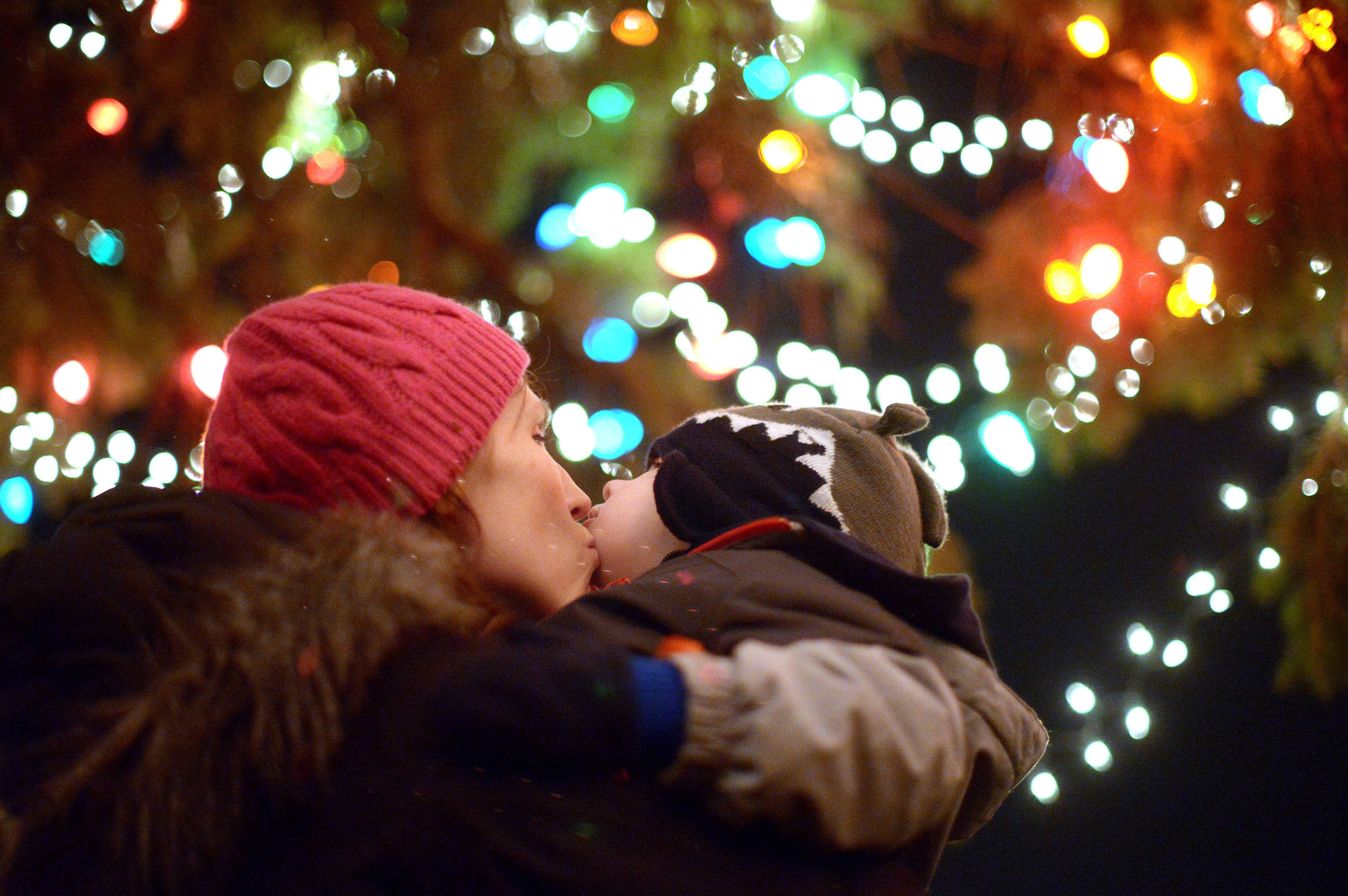 Matthew Koenig, 3, of St. Charles gets a peck on the cheek from his mother, Erin, underneath the Geneva Christmas tree on Third Stree in downtown Geneva Friday. This is the first time they've attended the annual event.