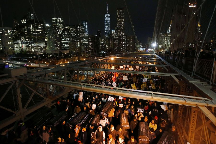 Protesters rallying against a grand jury's decision not to indict the police officer involved in the death of Eric Garner carry a collection of mock coffins bearing the names of victims of fatal police encounters as they cross the eastbound traffic lanes of the Brooklyn Bridge, Thursday, Dec. 4, 2014, in New York.