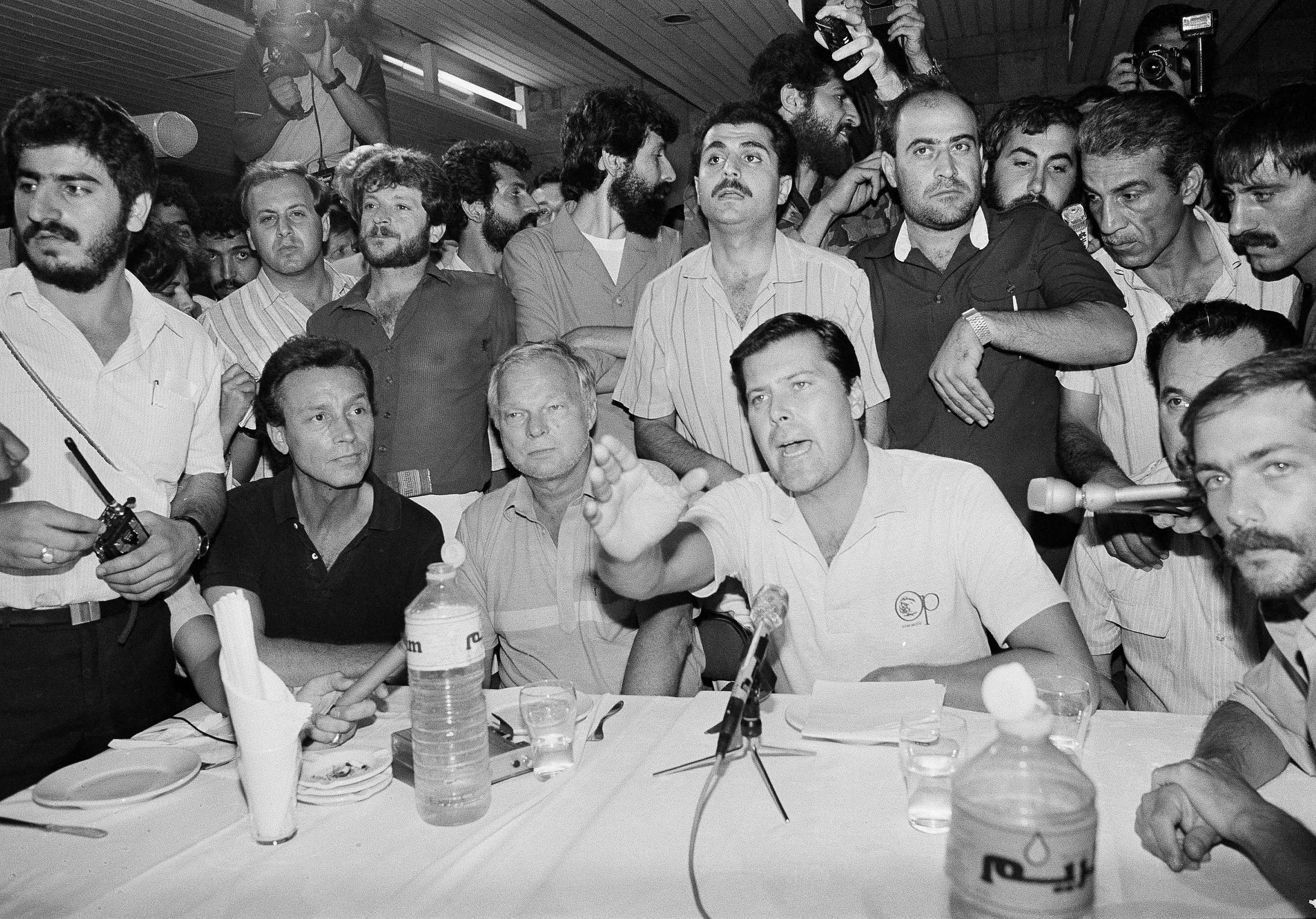 Hostage Allyn Conwell, 39, of Houston, Texas, waves his hand and yells as he replies to reporters' questions during a news conference at Beirut International Airport June 20, 1985. Journalists were pushed and shoved by Shiite Muslim AMAL Militiamen away from the five hostages. The Americans were among 40 hostages taken during the hijacking of TWA flight 847 from Athens to Rome. Sitting to Conwell's right is Peter Hill, 57, of Hoffman Estates, Thomas Cullins, 42, Burlington, Vermont. At his left is Arthur Toga, 33, of St. Louis.