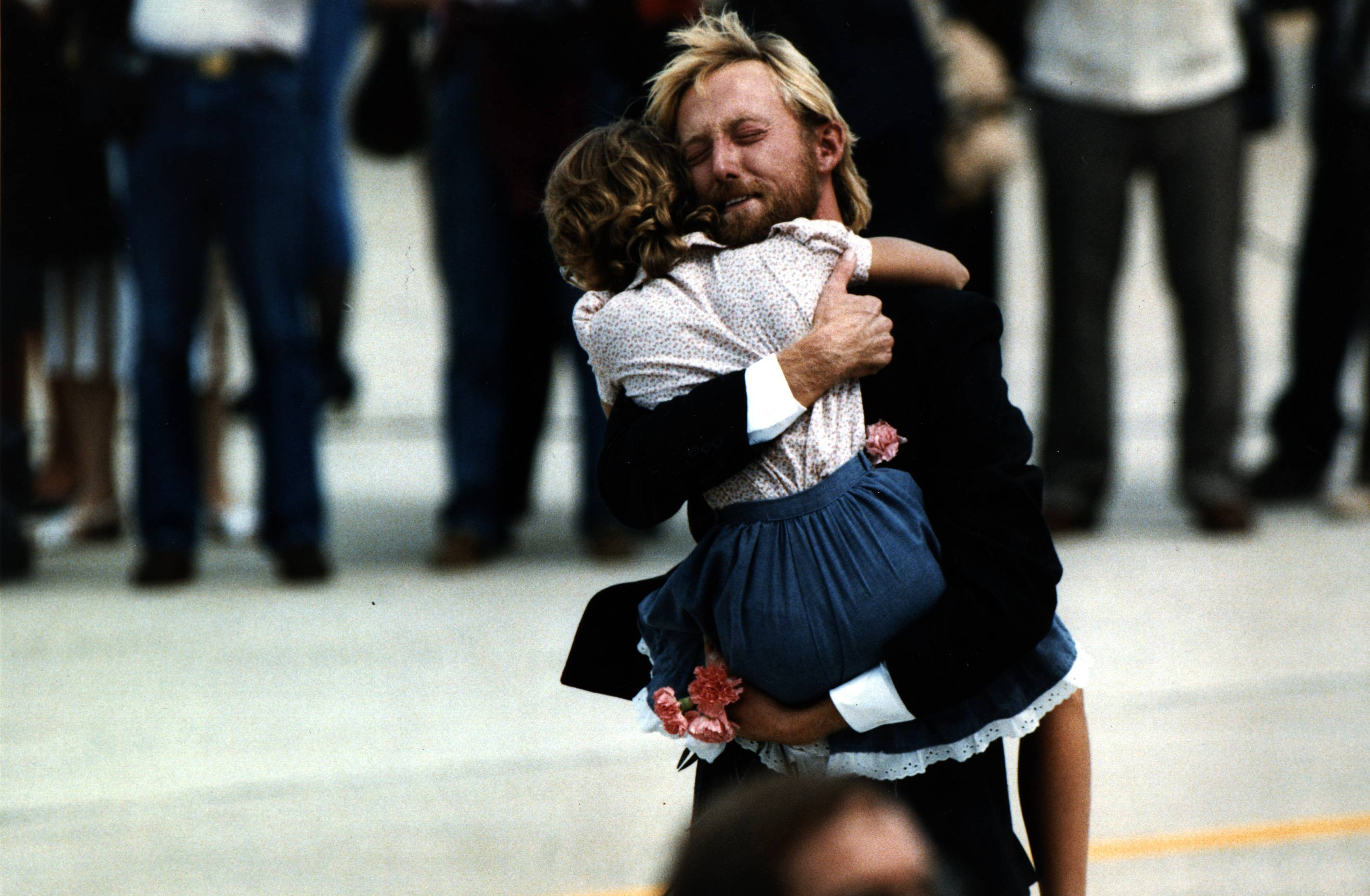 While holding carnations he carried off the plane, former TWA flight 847 hostage Victor Amburgy hugs an unidentified girl after his arrival at Andrews Air Force Base. Thirty former hostages from the flight were greeted on American soil by President Ronald Reagan and first lady Nancy Reagan.