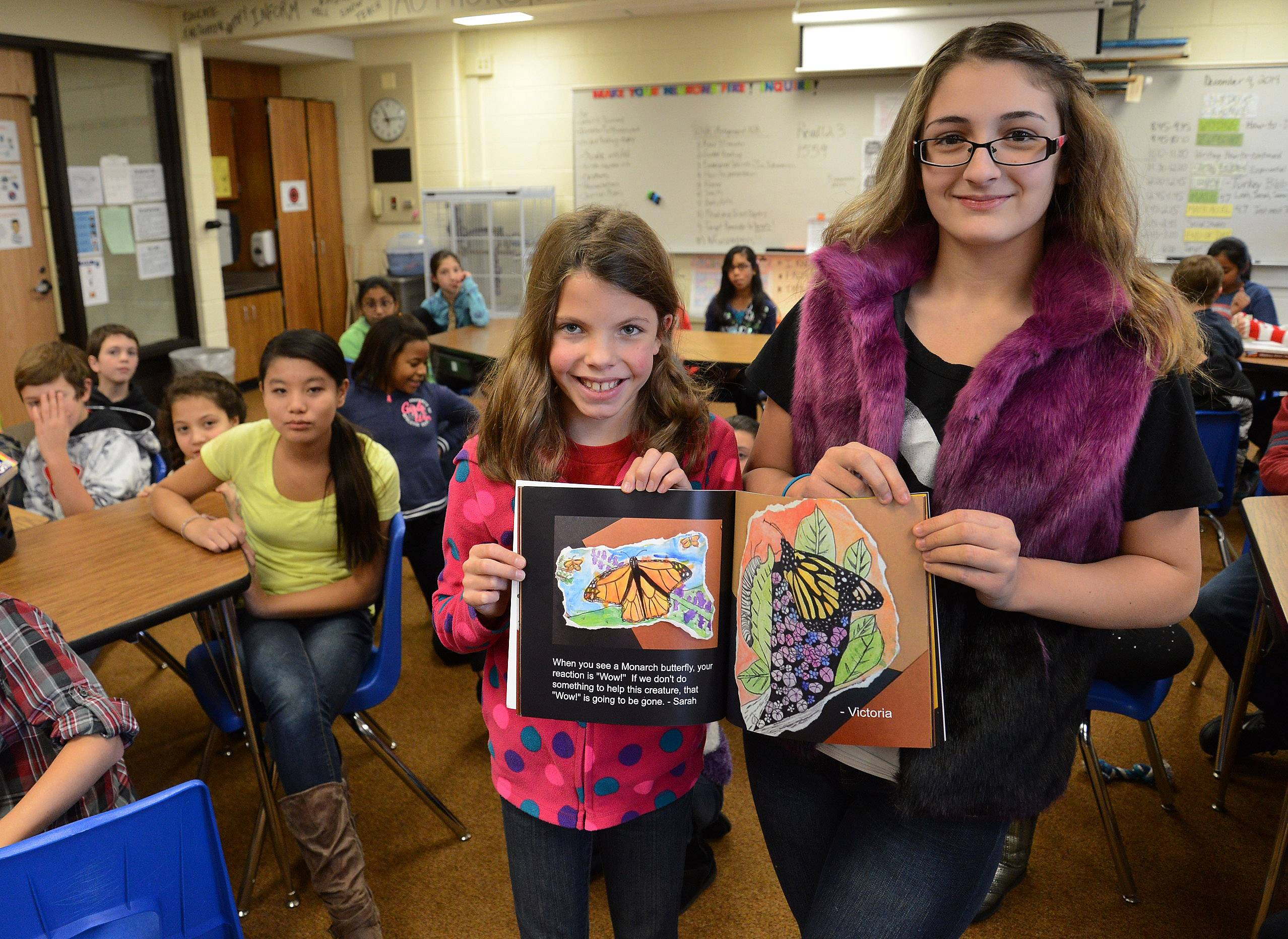 Sarah Carr, left, and Victoria Atanassova show their drawings that are part of an illustrated book their class produced as part of the monarch butterfly project at Michael Collins Elementary School in Schaumburg.