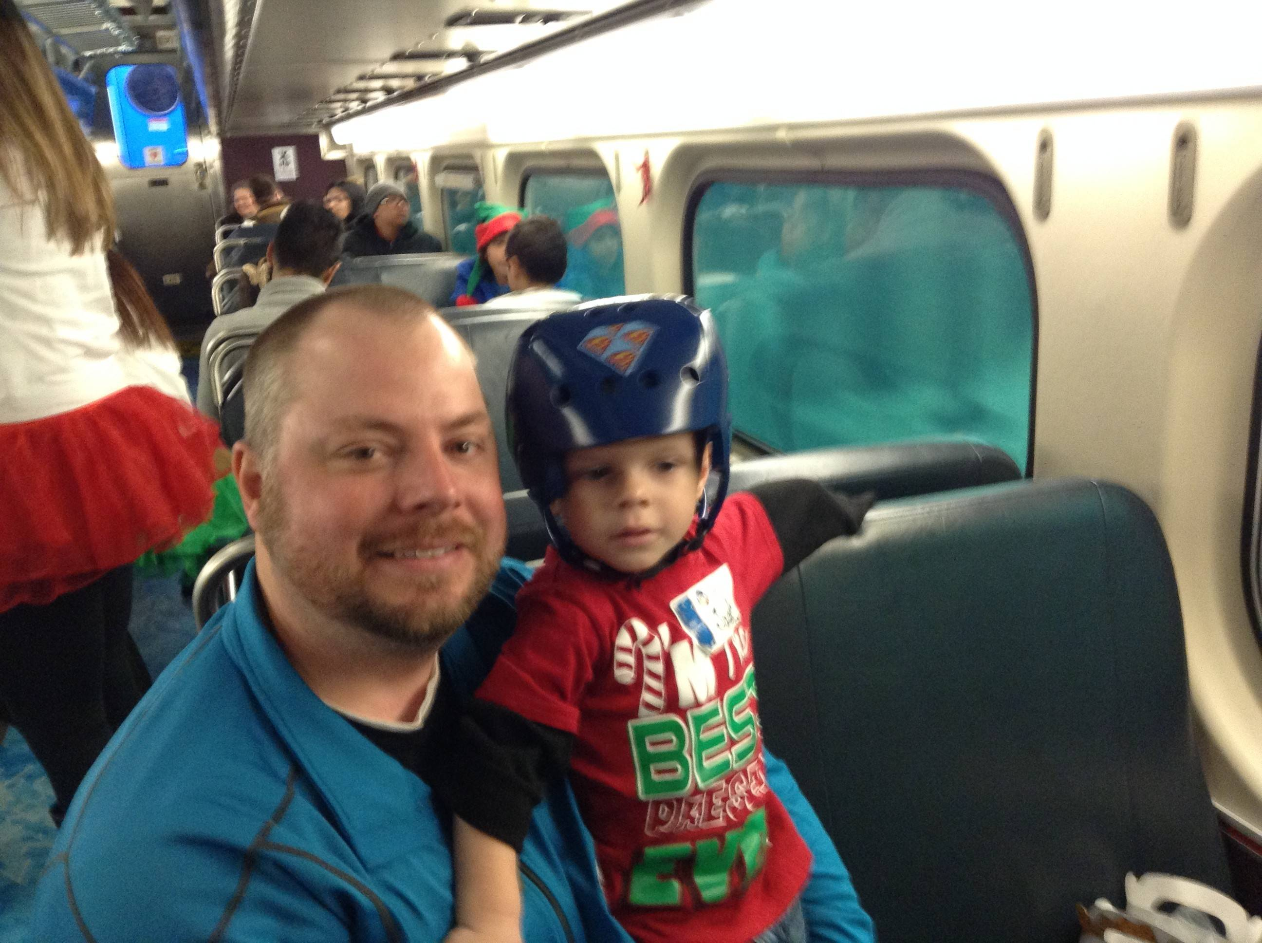 Jack Speichet, 2, takes a break from the activities aboard the Operation North Pole train with his dad, Timothy.
