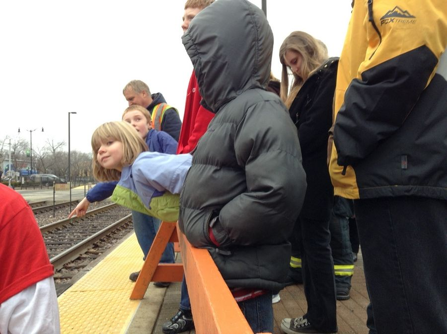 Abby Peters and her brothers look down the platform for the first glimpse of the Operation North Pole train Saturday at the Des Plaines Metra station.