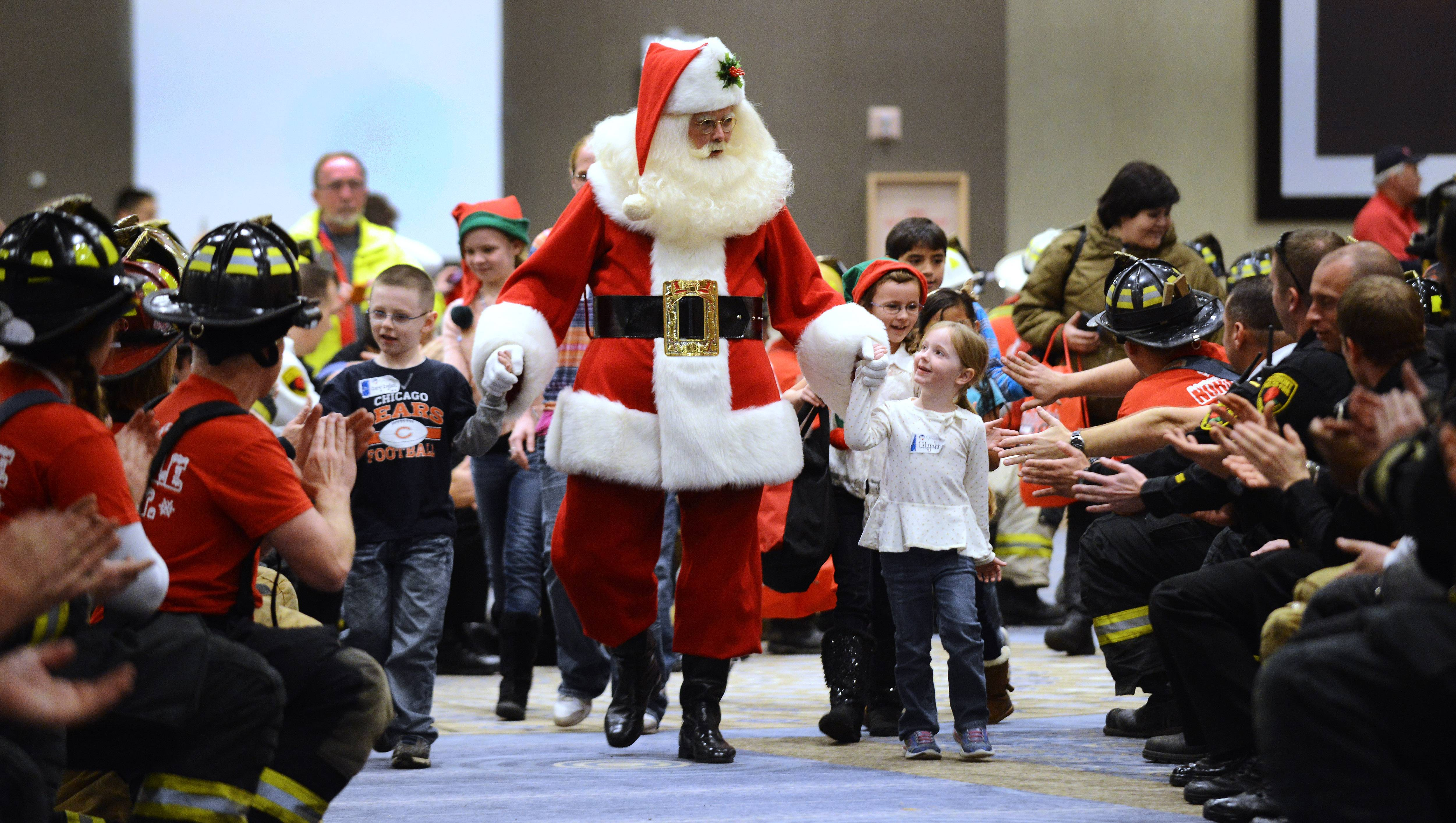Members of the Rosemont fire and police departments greet Santa and the children as they arrive at the Stephens Convention Center as part of Operation North Pole, an event for children with life-threatening illnesses Saturday.