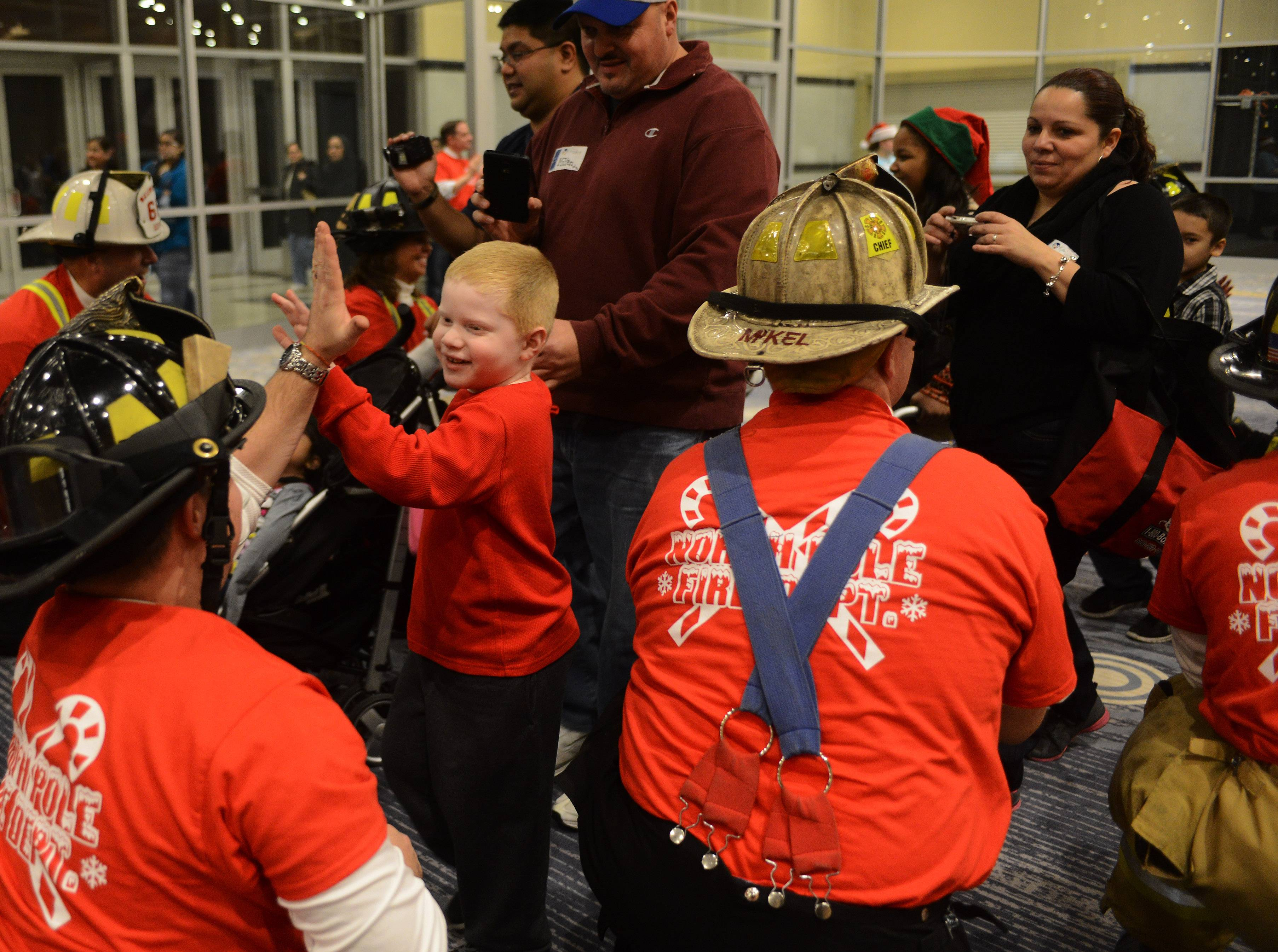 Members of the Rosemont fire and police departments greet children as they arrive at the Stephens Convention Center as part of Operation North Pole, an event for children with life-threatening illnesses and their families.