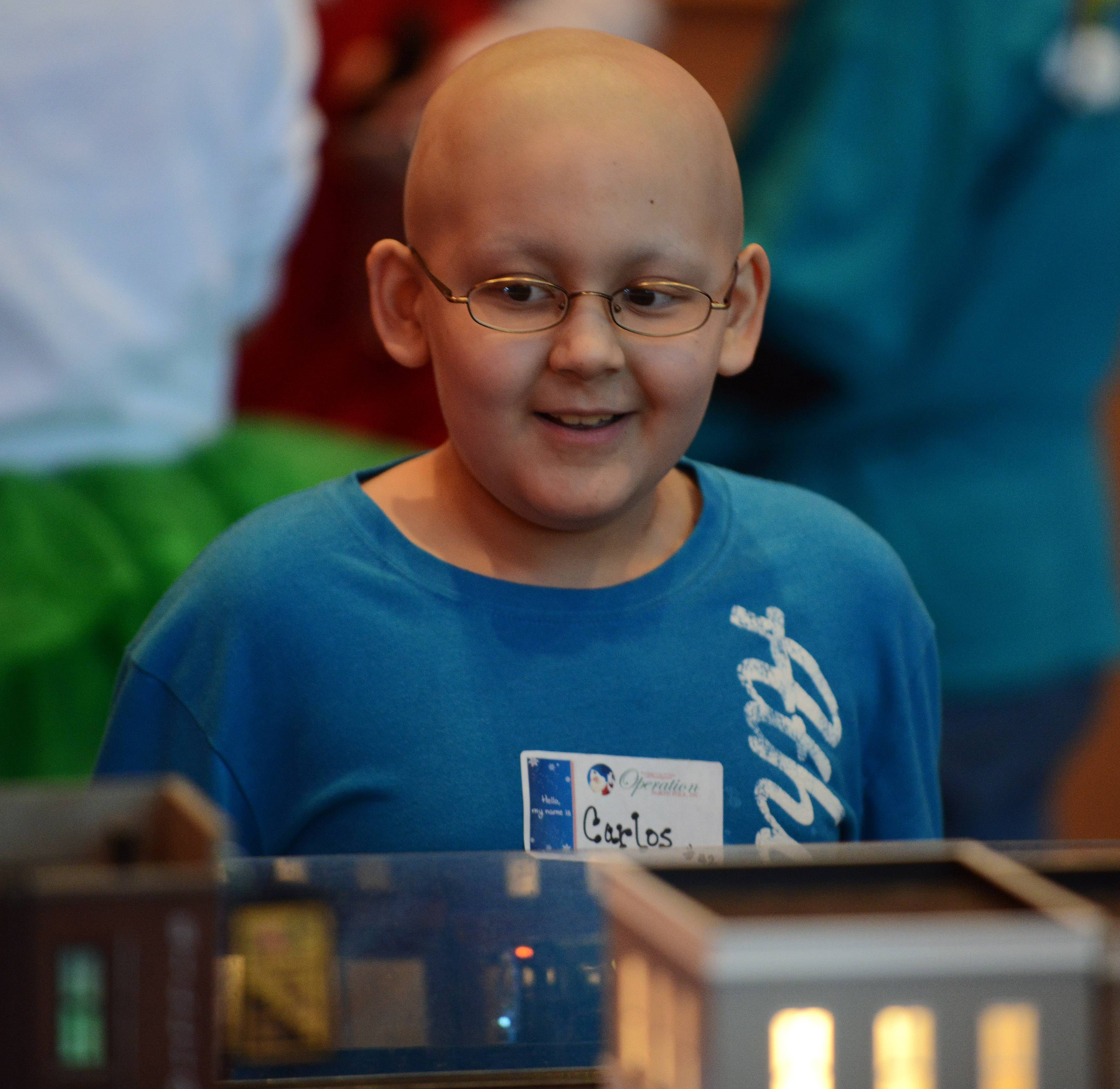 Carlos Romero, 7, of Aurora is thrilled with some model trains as part of Operation North Pole, an event for children with life-threatening illnesses.
