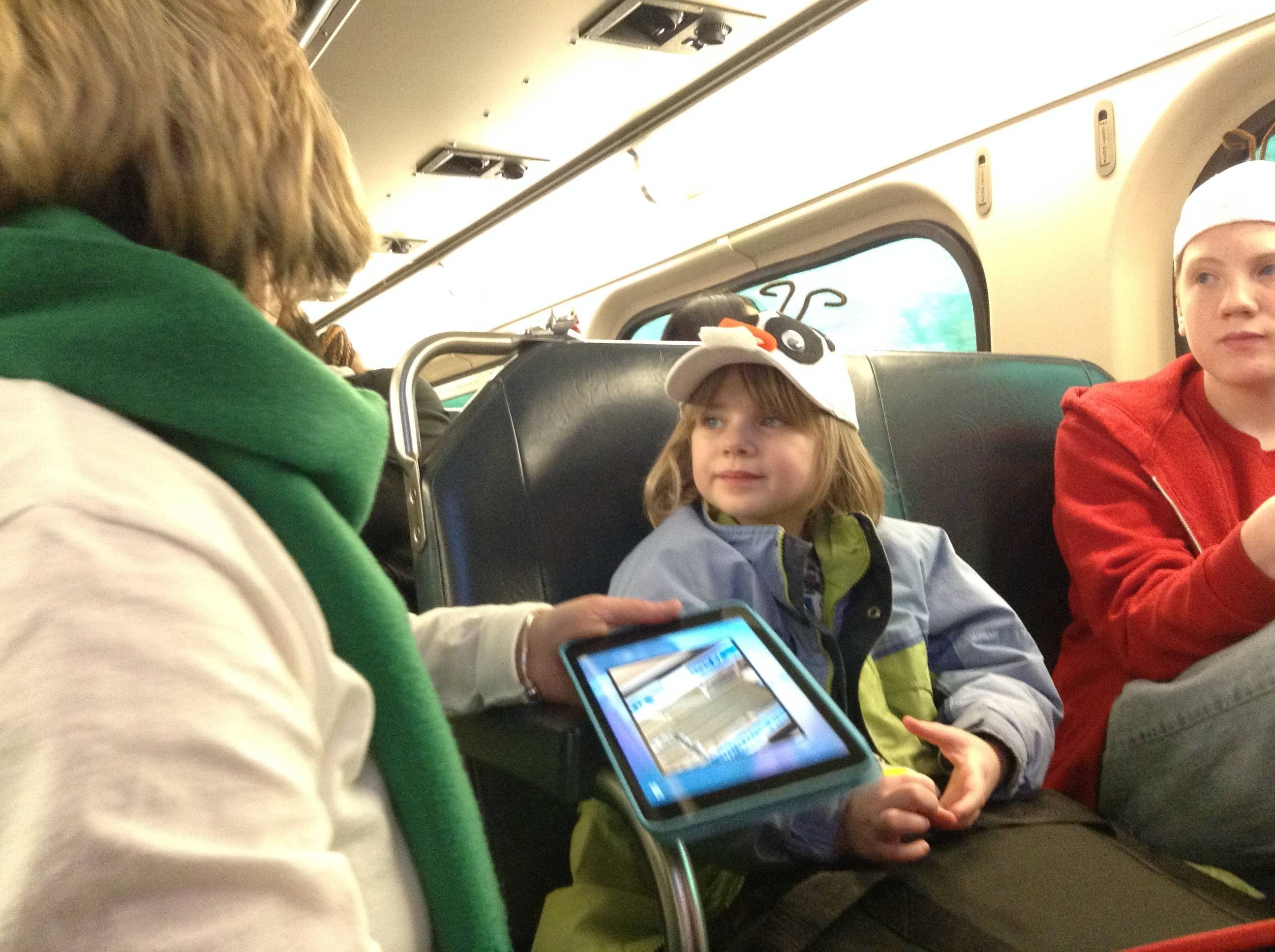 Abby Peters, 5, and big brother Samuel, 12, of North Aurora are greeted by one of the many elves aboard the Operation North Pole train Saturday.