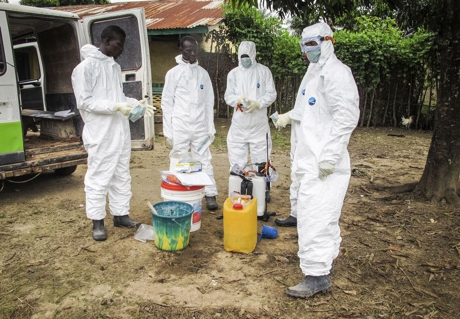 Health workers wear protective gear before entering the house of a person suspected to have died of the Ebola virus in Port Loko Community situated on the outskirts of Freetown, Sierra Leone.