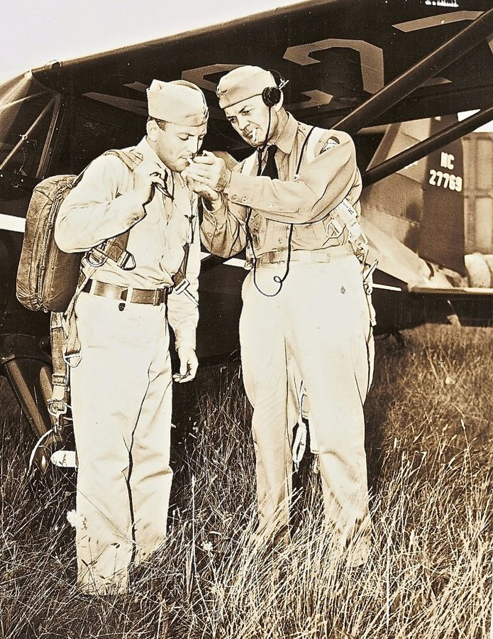The founder of the Civil Air Patrol in 1941, Gill Robb Wilson, right, shares a light with another civilian volunteer.