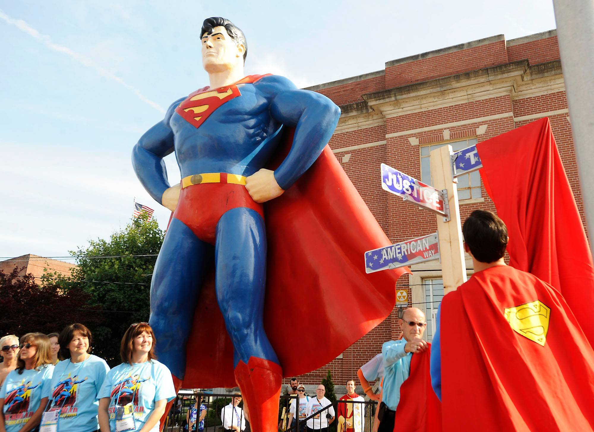 "At the 2012 Superman Celebration in Metropolis, Illinois, Mayor Billy McDaniel and Josh Boultinghouse, the official Superman of the celebration, unveil a street sign marking ""American Way."" In popular culture, many superheroes, like Superman, keep their real identities secret to protect their loved ones and themselves -- and because it's expected in superhero stories."