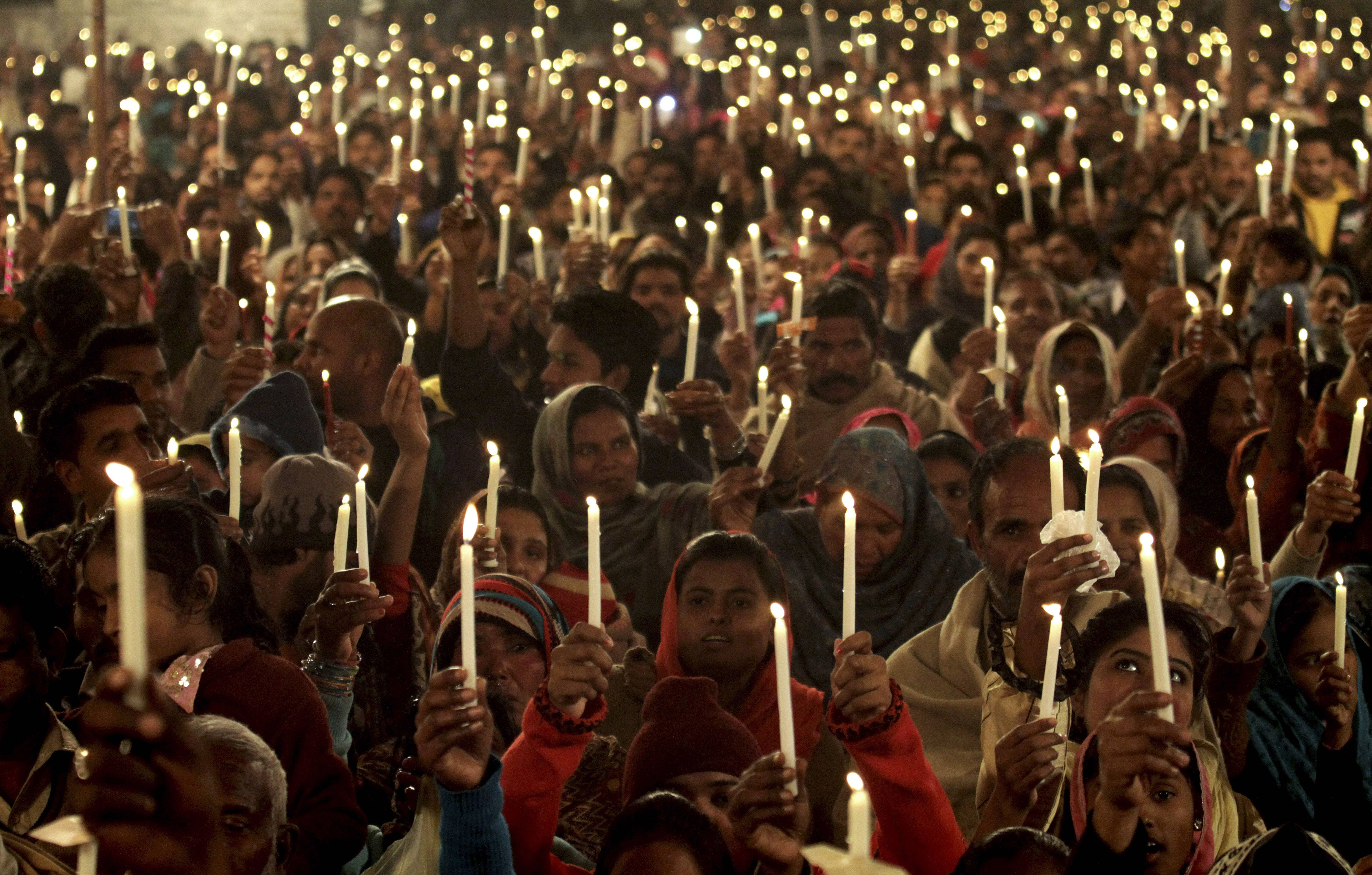 Pakistani Christians hold up candles to pay tribute to the victims killed in Tuesday's Taliban attack on a military-run school in Peshawar, as they participate in candle light vigil Wednesday, Dec. 17, 2014 in Lahore, Pakistan.