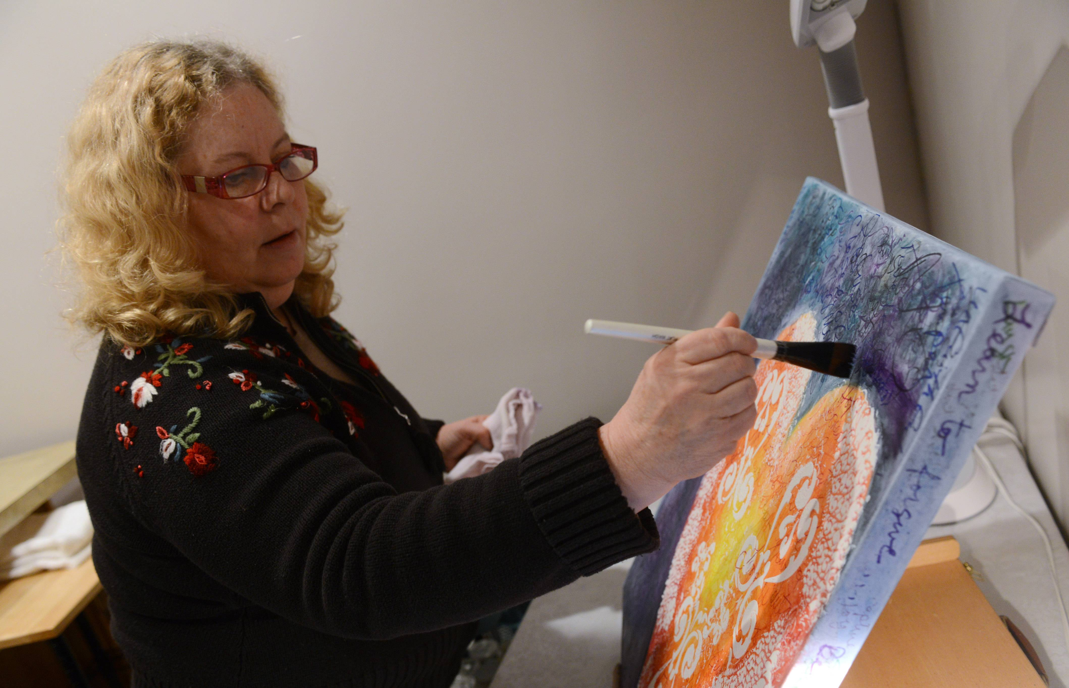 Linda Kay works on a painting in a studio she shares with another artist.