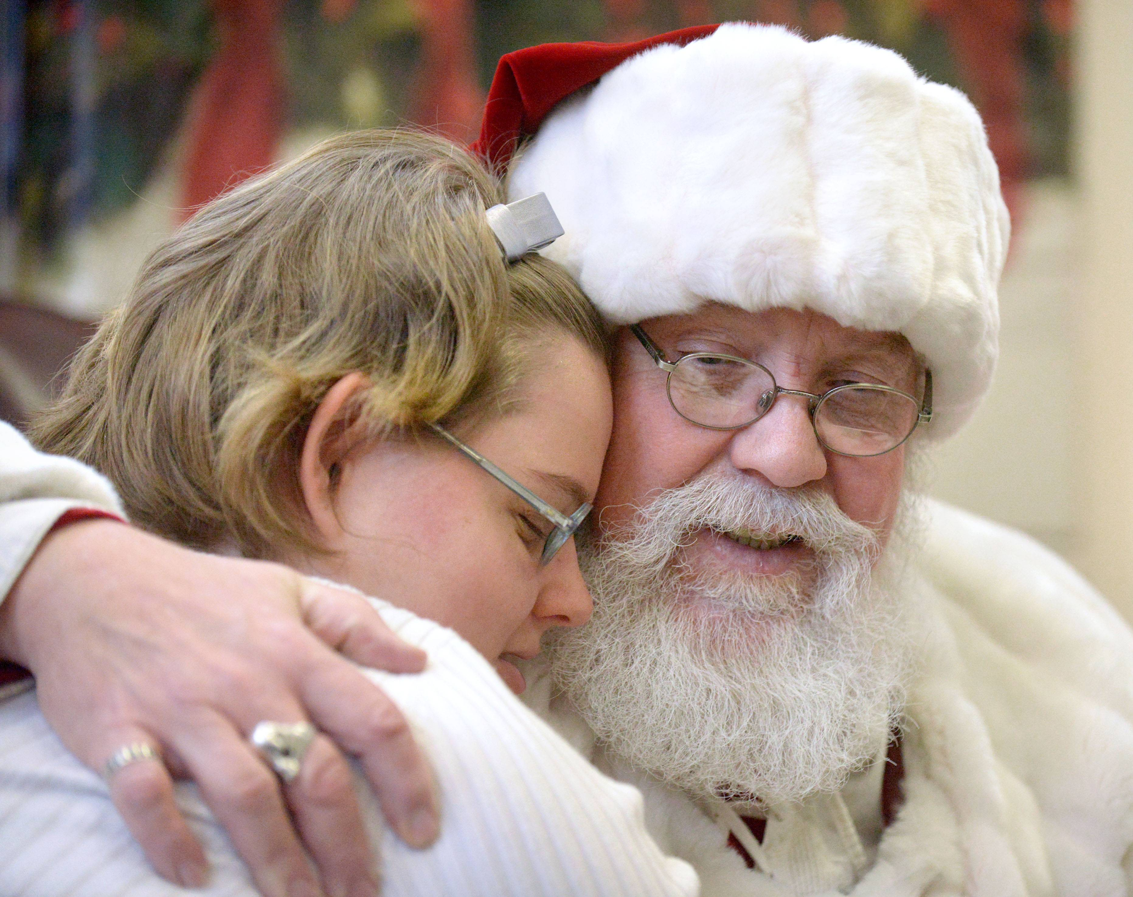 "Sydney Gajewski, 19, of South Elgin hugs Santa (school bus driver Greg Stout of Elgin) after telling him her wish list during his visit Wednesday to South Elgin High School. Her wish was ""Good health and peace for all."""