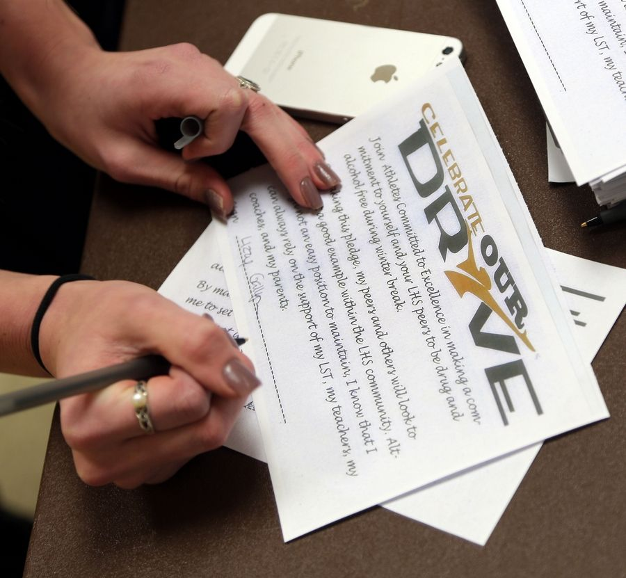 Libertyville High School's Athletes Committed to Excellence club asked their fellow students to sign pledges to make responsible choices during the upcoming winter break Thursday.