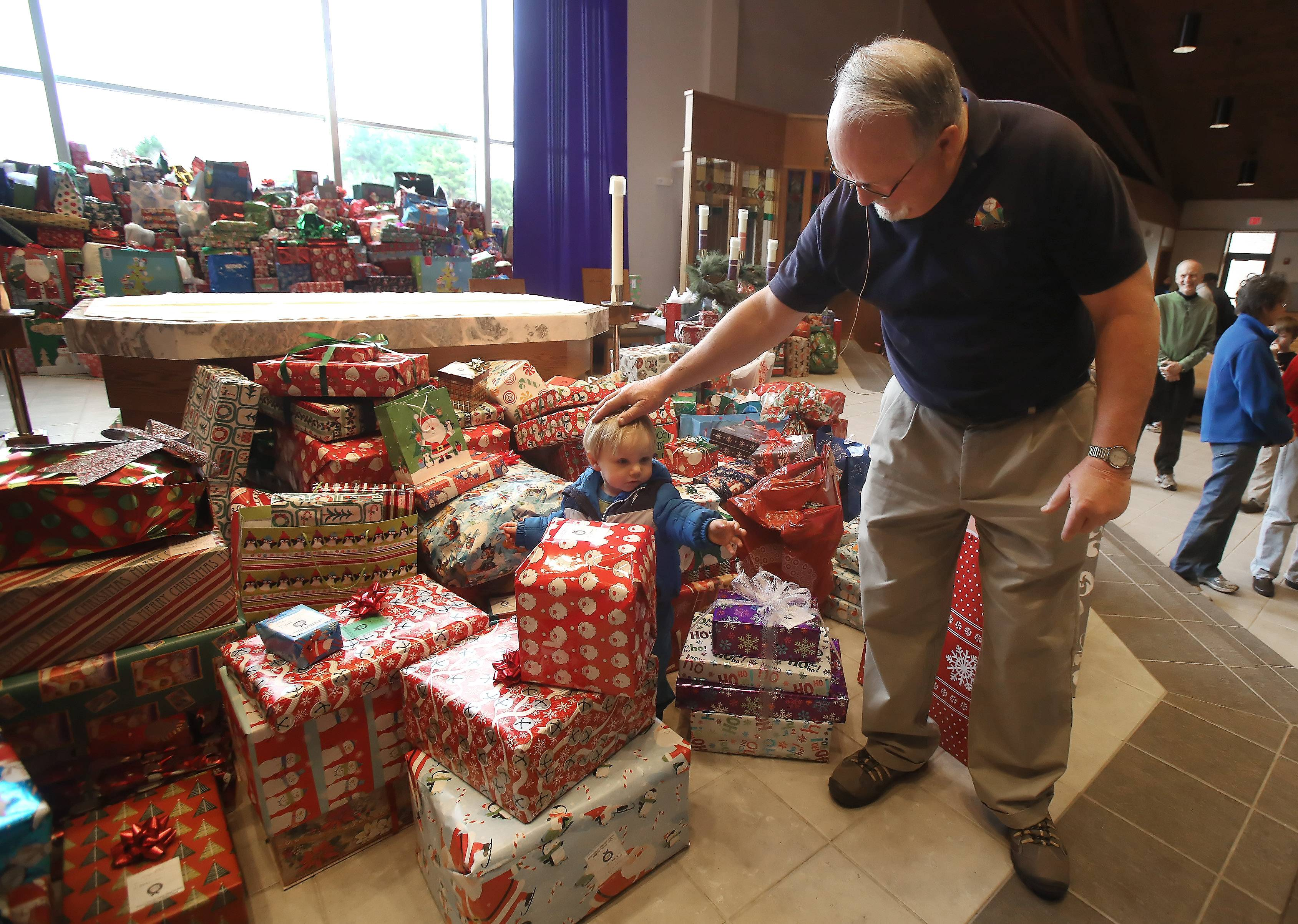 Jim Wogan walks with David Morvig, 2, of Vernon Hills as they examine gifts donated during Gift Sunday at St. Mary of Vernon Catholic Church in Indian Creek. The church was expected to collect gifts for more than 1,000 low-income people for the holidays.