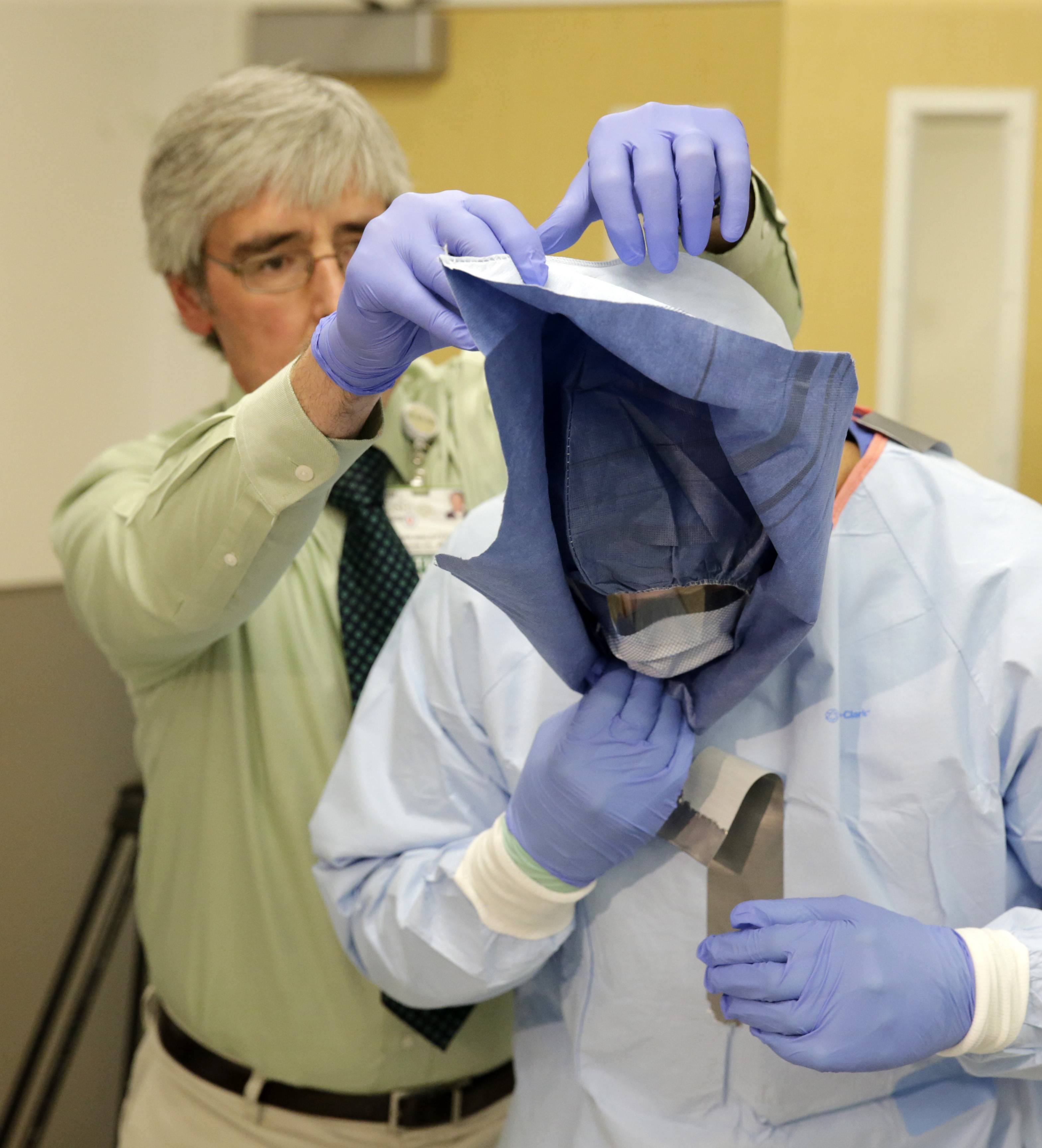 Nurse Keene Roadman demonstrates how to remove protective equipment during a training session for doctors and nurses who might handle Ebola cases at Rush University Medical Center.