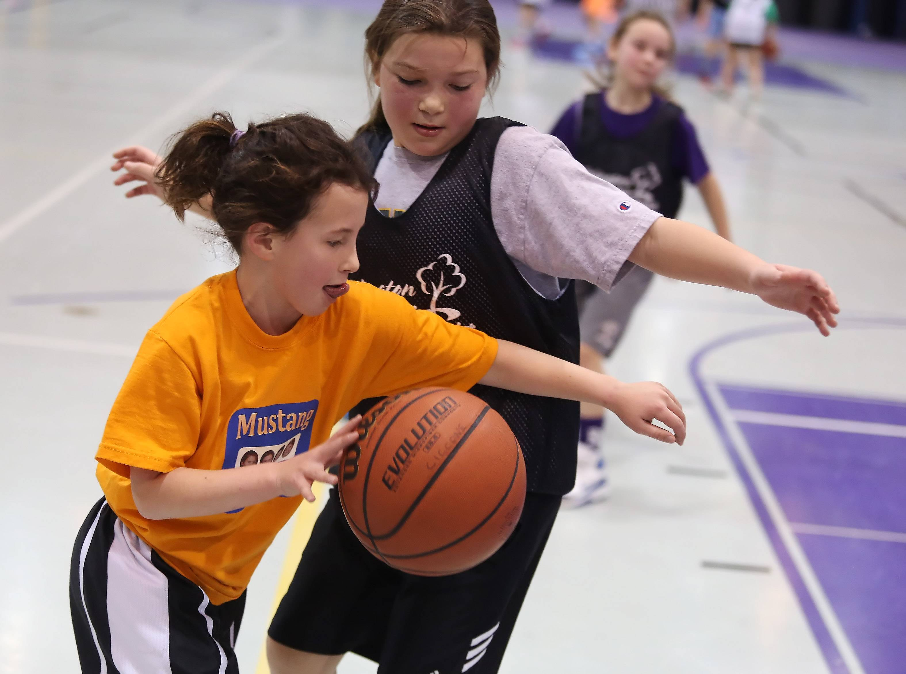 Third-grader Julia Ingemunson, left, of the Mustang MAJK tries to dribble around fourth-grader Caroline Ciccone of the Spartans during Sunday's Mustang 3-on-3 Shootout at Rolling Meadows High School.