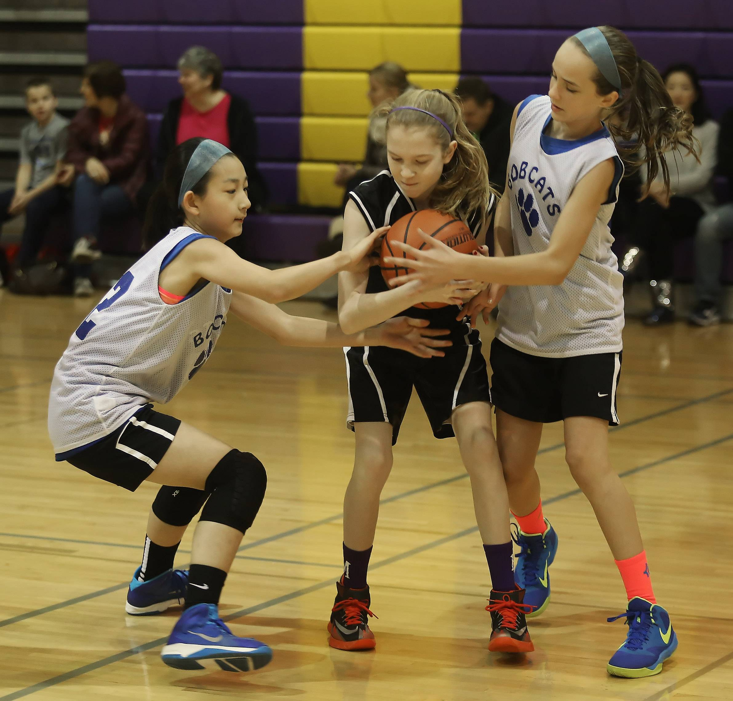 Seventh-grade Bobcats players Yunah Shin, left, and Margueret Spear of Palatine try to take the ball away from GEEK player Erin Behls of Arlington Heights during the annual Mustang 3-on-3 Mustang Shootout on Sunday at Rolling Meadows High School. The Rolling Meadows High School Booster Club sponsored the event.