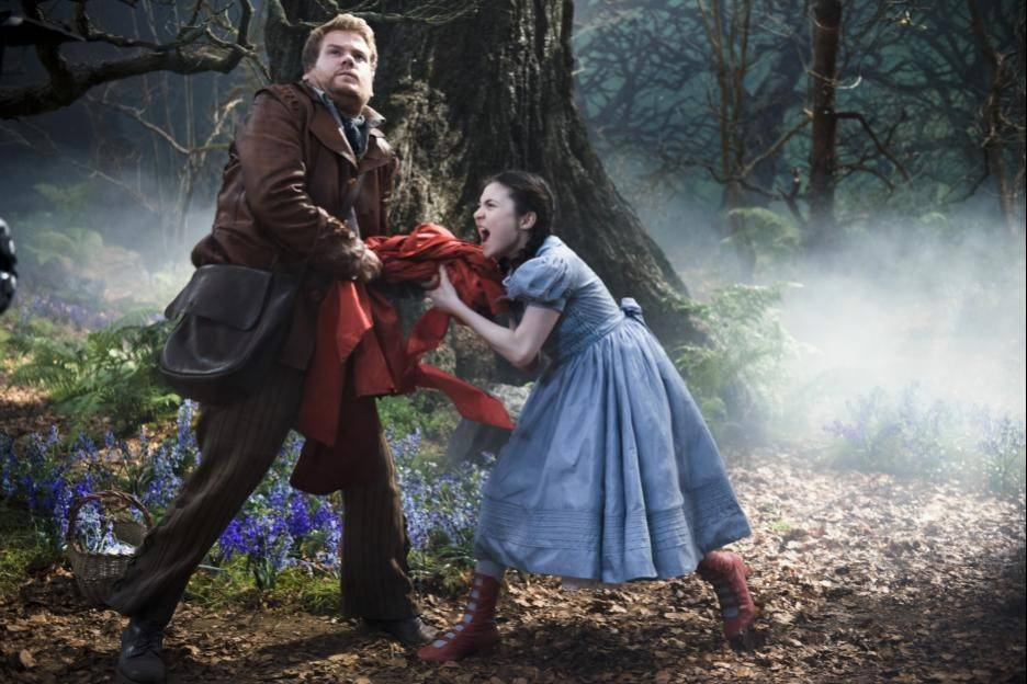"The baker (James Corden) attempts to steal the red riding hood from Red Riding Hood (Lilla Crawford) in Rob Marshall's ""Into the Woods."""