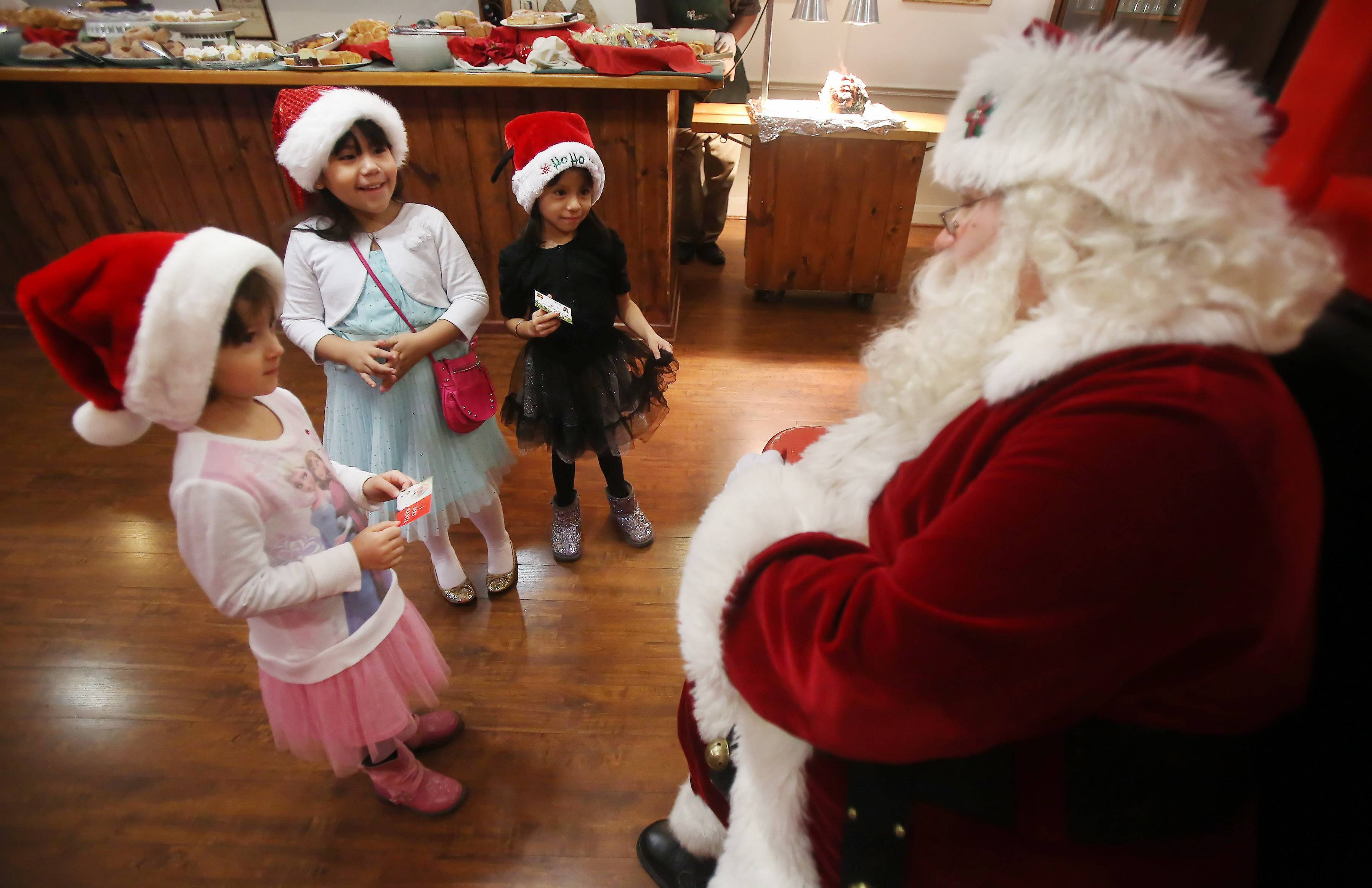 Maria Ritacca, 5, left, Maggie Campos, 6, and Ashley Mora, 6, all of Highwood, talk with Santa Claus during Breakfast With Santa Sunday at Lambs Farm in Libertyville. Families enjoyed a buffet brunch and children then had a chance to visit with Santa Claus.