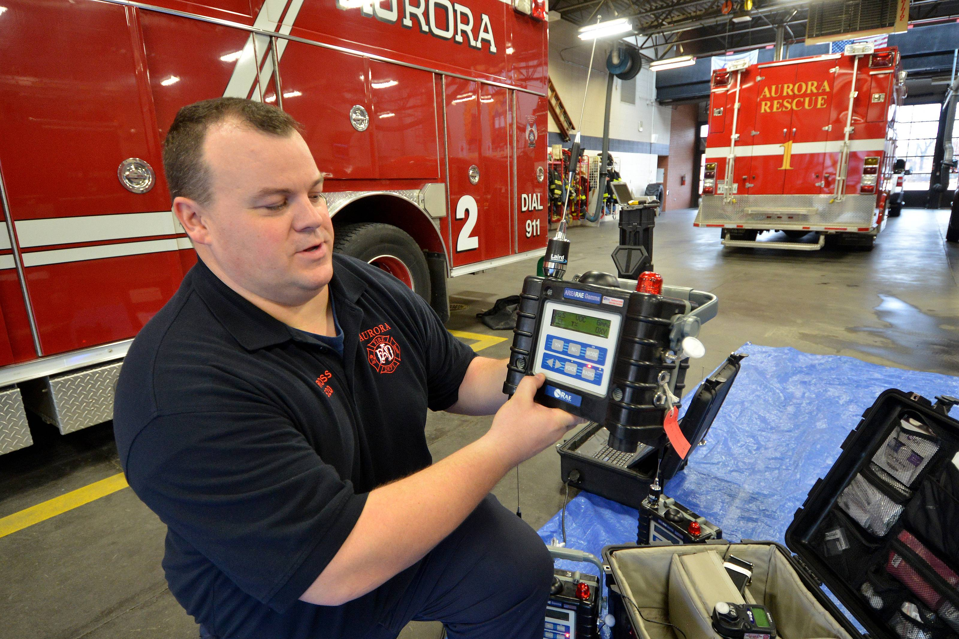 Aurora firefighter/paramedic John Ross, a hazmat specialist, demonstrates equipment that detects and identifies hazardous chemicals.